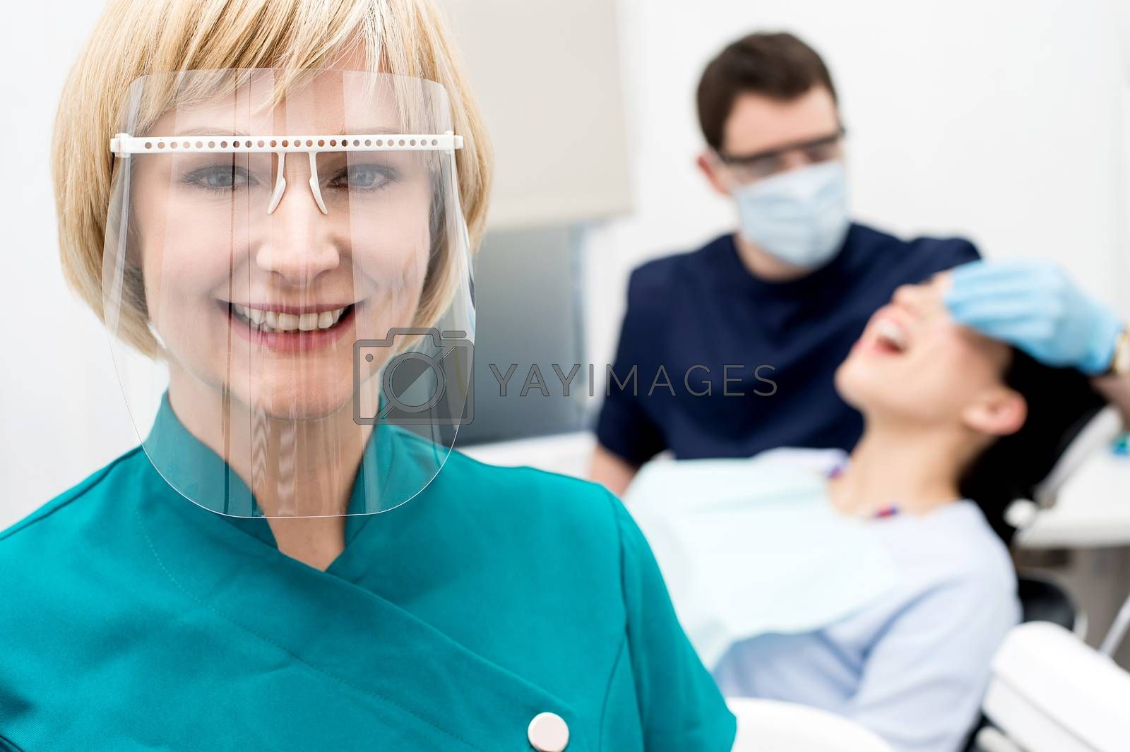 Woman assistant posing, behind dentist treating patient