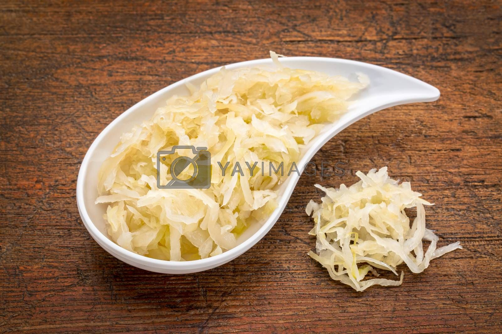 teardrop shaped bowl of sauerkraut against rustic wood - healthy eating concept