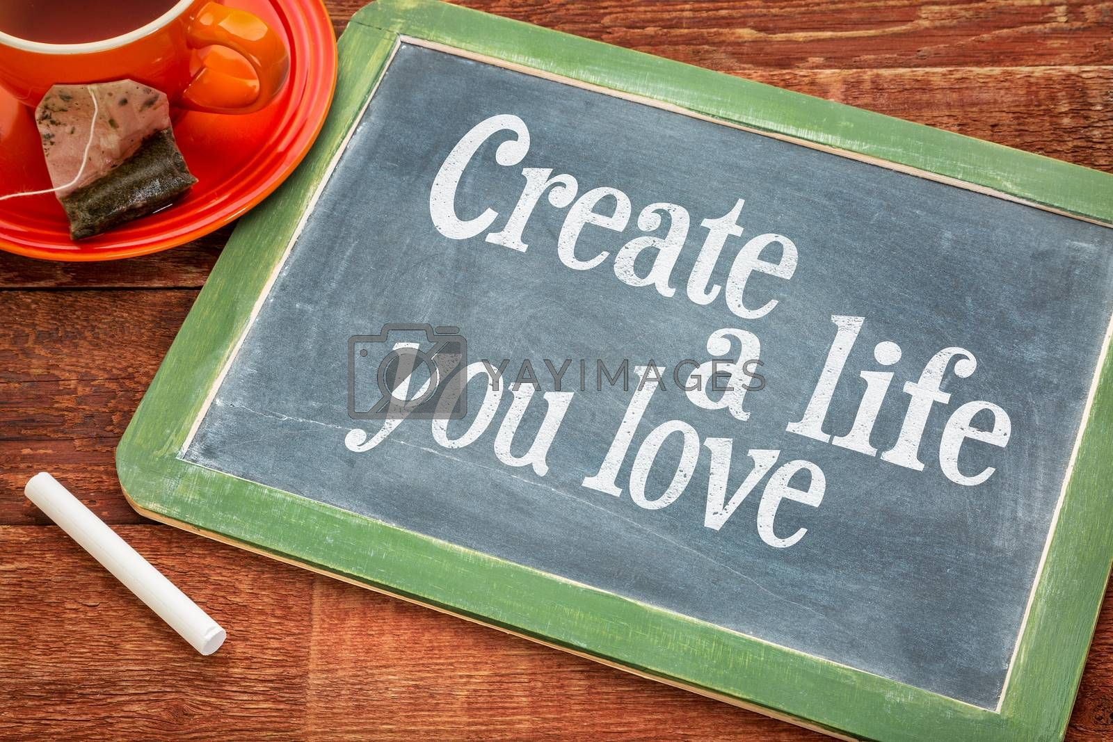 Create life you love motivational advice - text  on a slate blackboard with chalk and cup of tea
