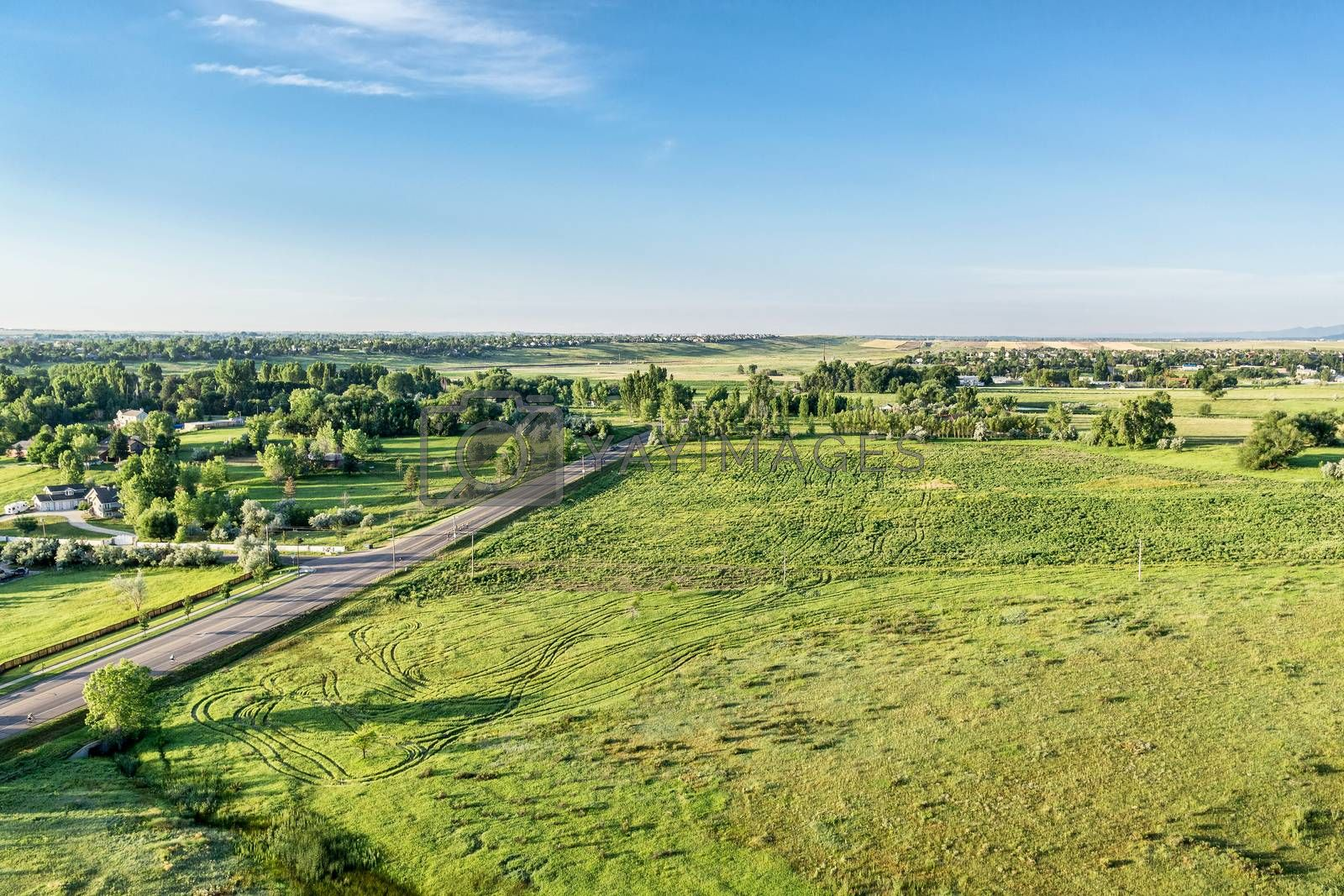 Aerial view of Rocky Mountains foothills near Fort Collins, Colorado with a green prairie, residential area and cyclist on a road