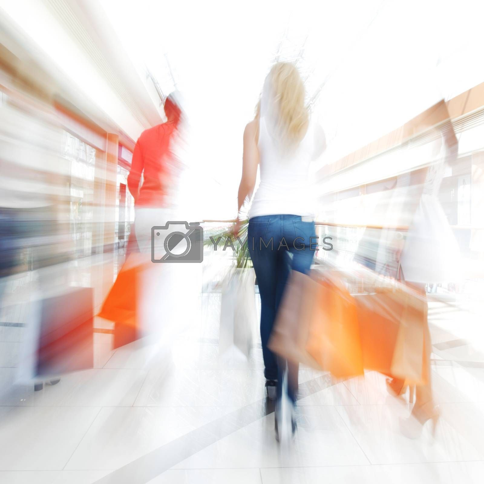 Women walking fast in shopping mall with bags