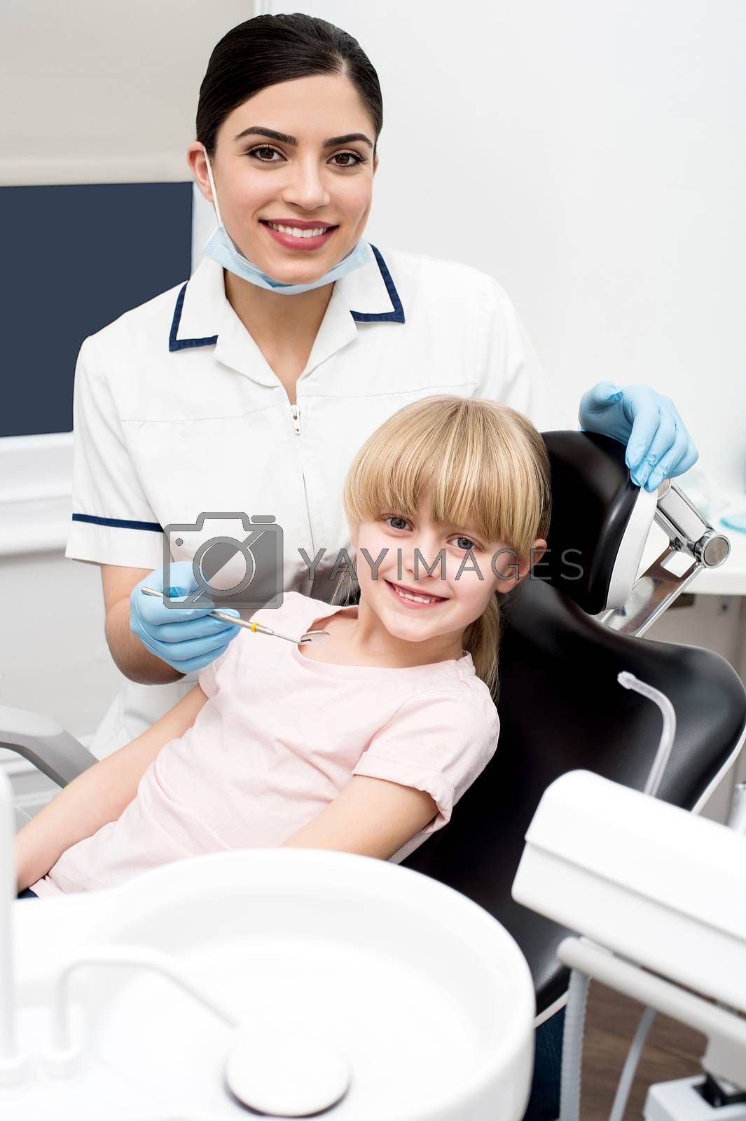 Dental assistant and little girl posing to camera