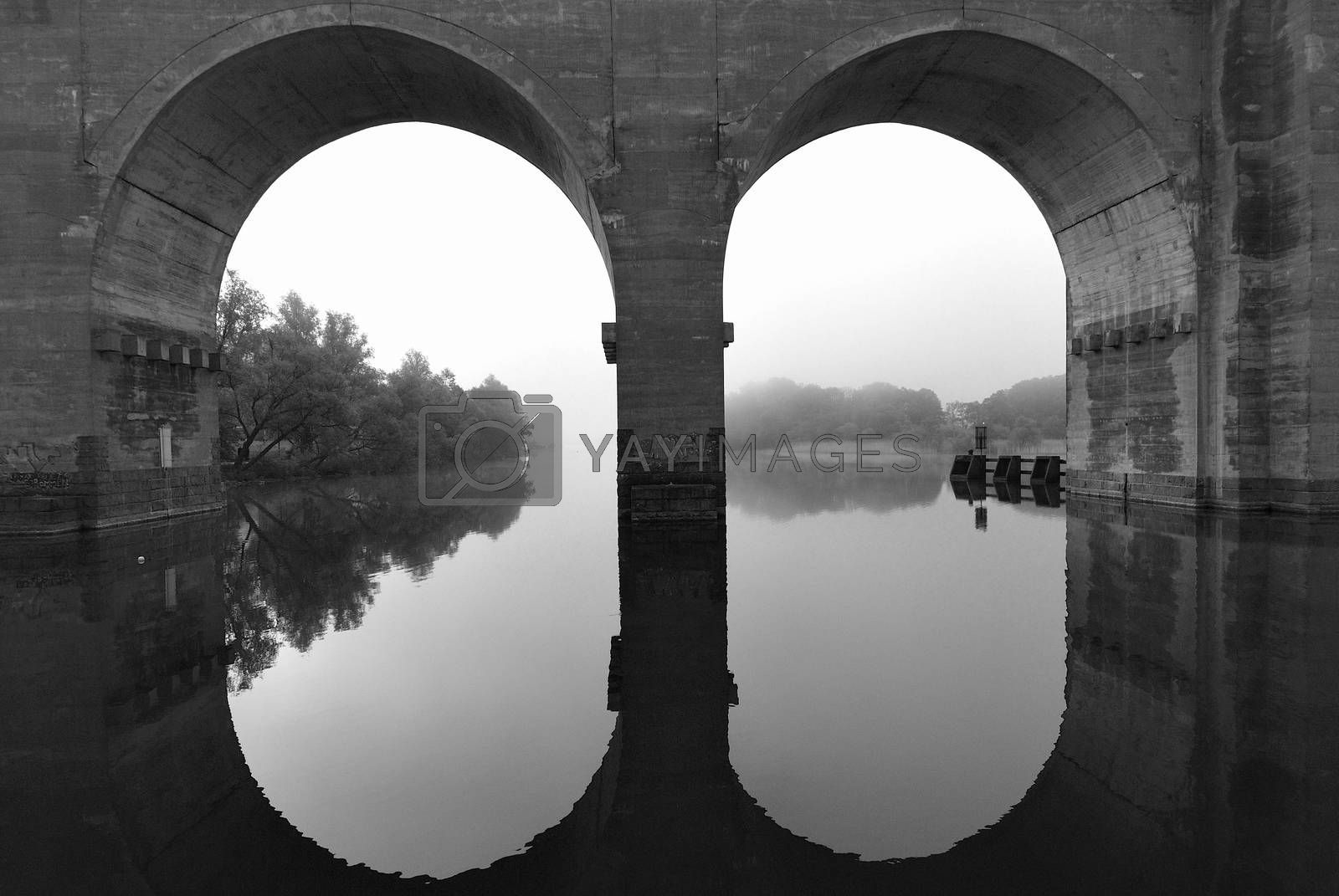An old bridge in Stockholm Sweden made of concrete. The vault mirroring in the water.