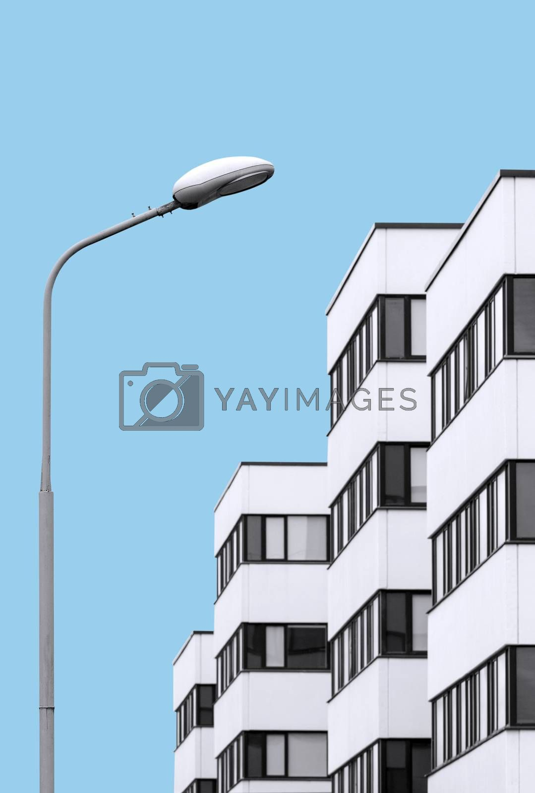 Abstract architecture concept on flat cyan color background. Residential house in the background and street lamp in focus in foreground