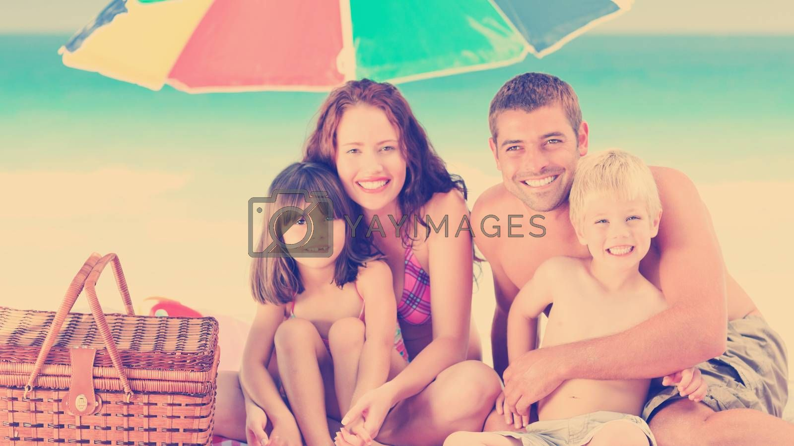 Family posing under a beach umbrella on the beach by Wavebreakmedia