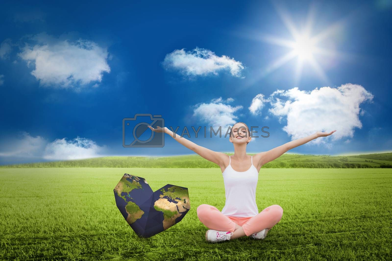 Woman sitting with arms raised  against sunny green landscape