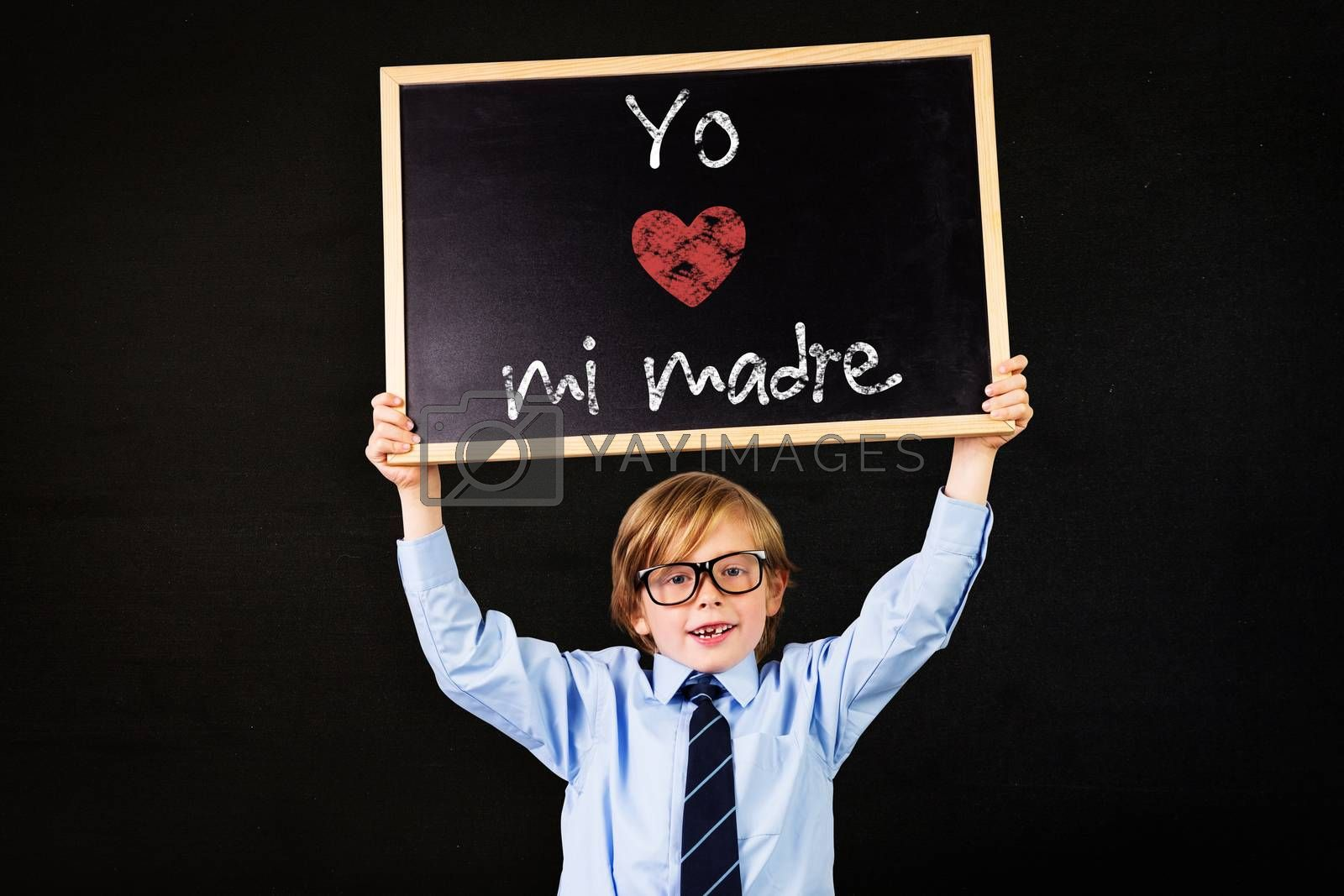 Cute pupil holding chalkboard against black