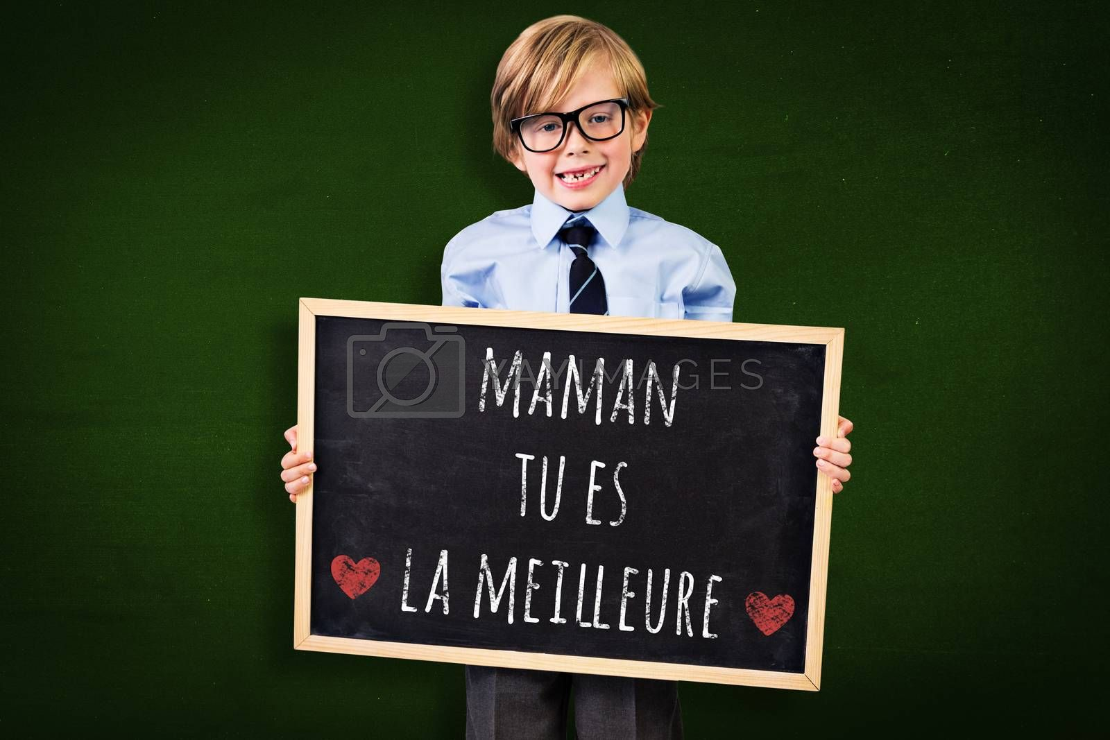 Cute pupil holding chalkboard against green