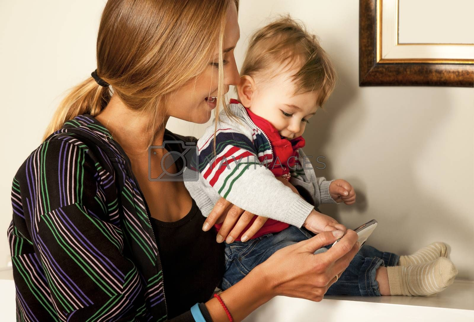 Young beautiful mother and her cute  little boy are looking and playing with a smartfone indoors. Copy space frame.