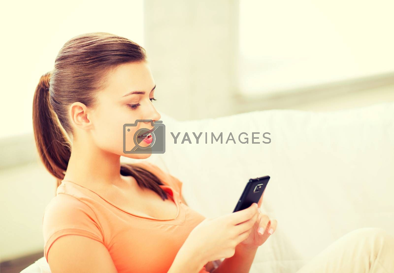 home, communication and internet - woman sitting on the couch with smartphone at home