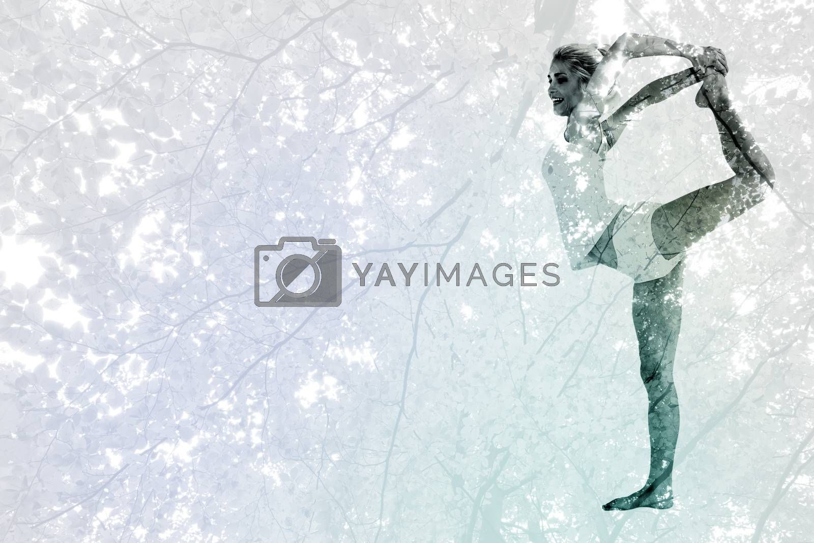 Sporty woman stretching body while balancing on one leg against branches and autumnal leaves