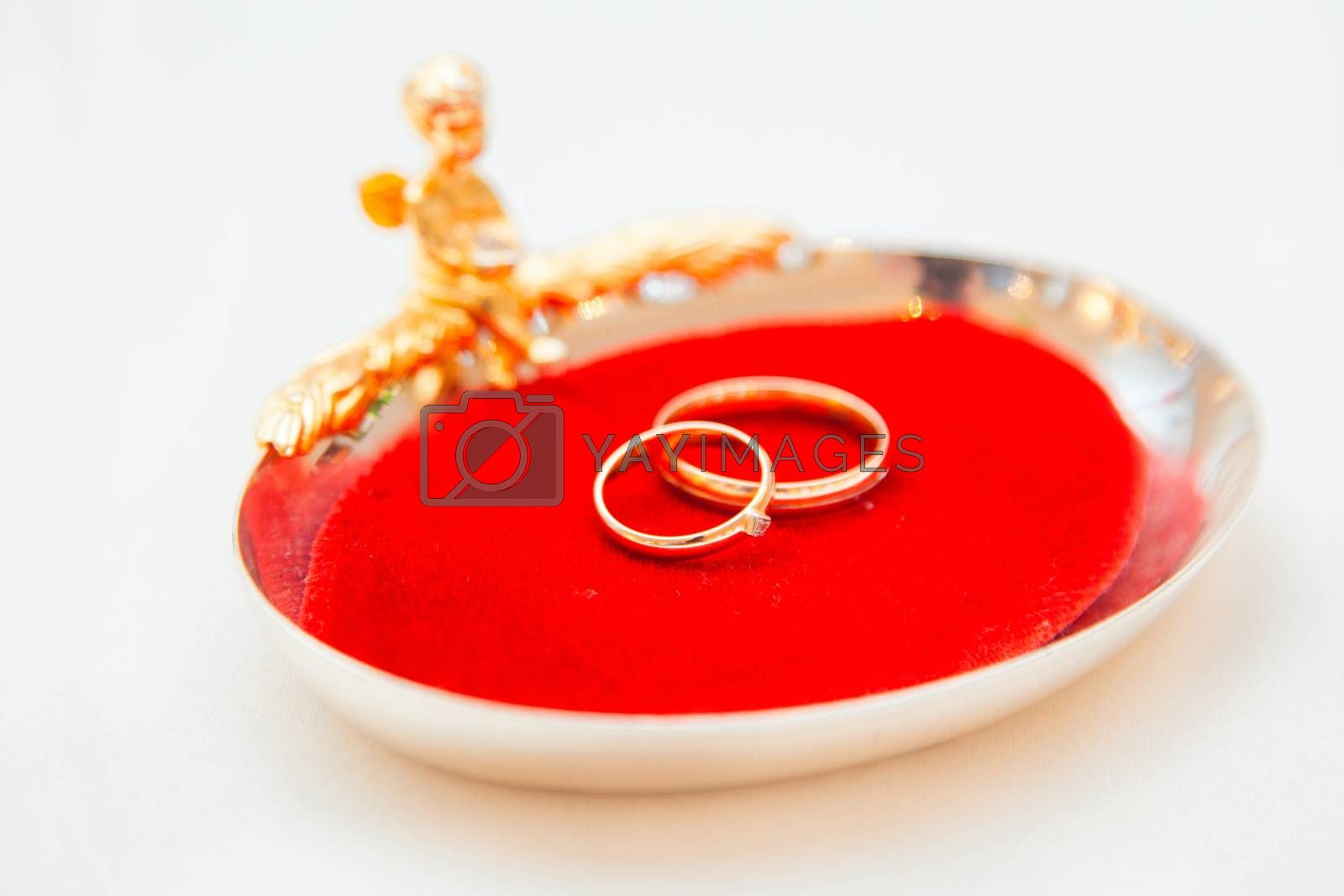 Two wedding rings on a red base with an angel.