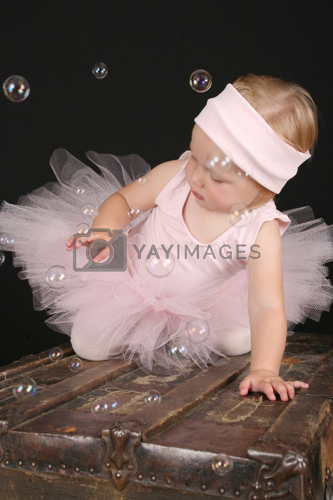 Blond girl wearing a ballet tutu playing with bubbles