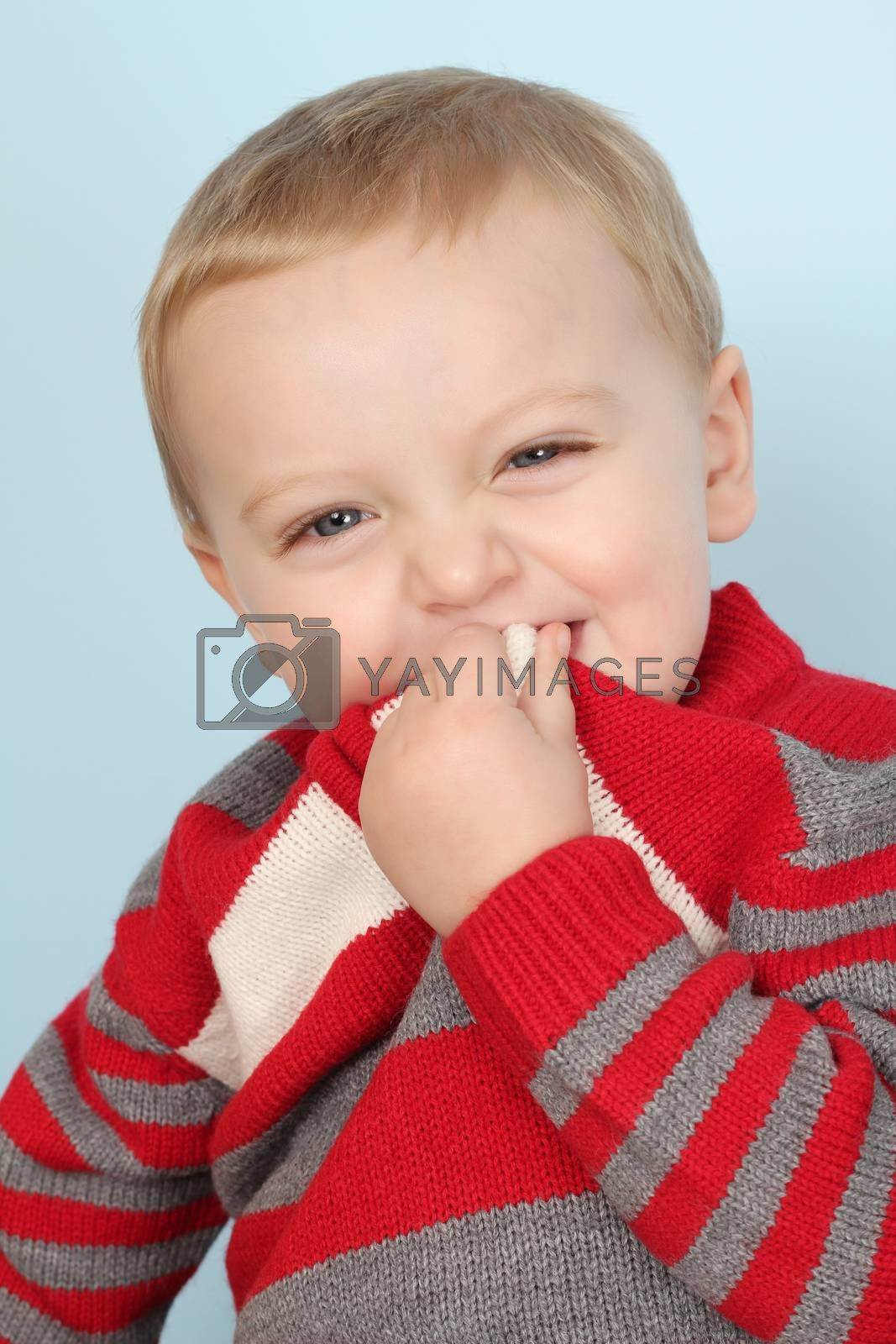 Blonde baby boy against a blue background
