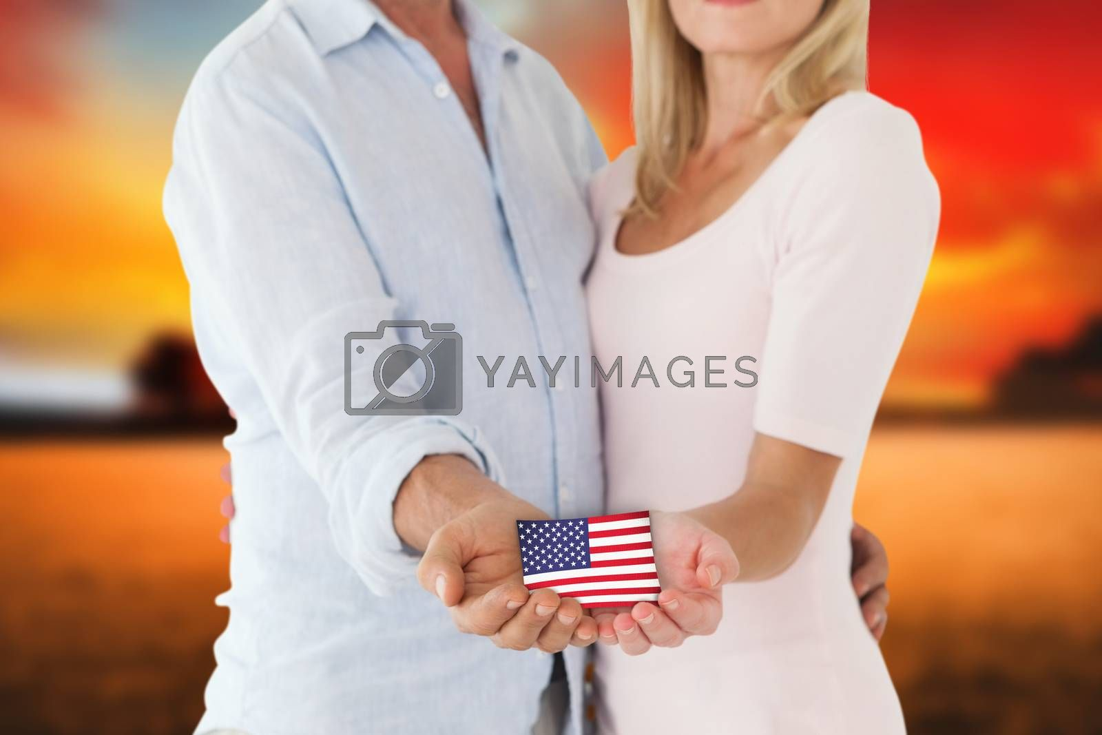 Happy couple holding their hands out against countryside scene