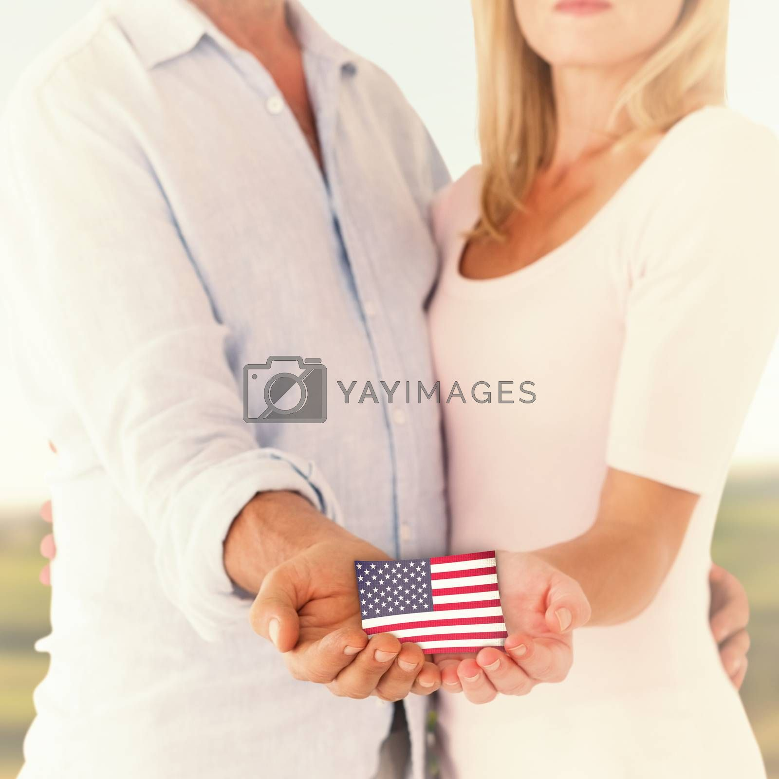 Happy couple holding their hands out against scenic landscape