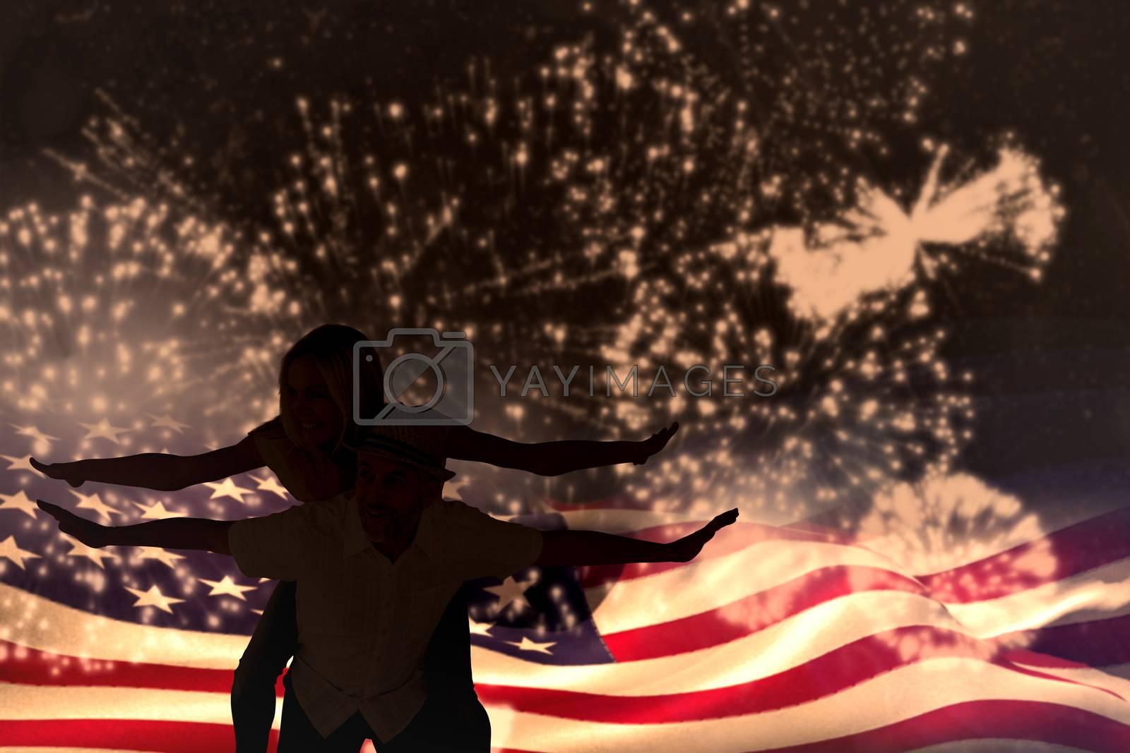 Happy man giving his partner a piggy back against white fireworks exploding on black background