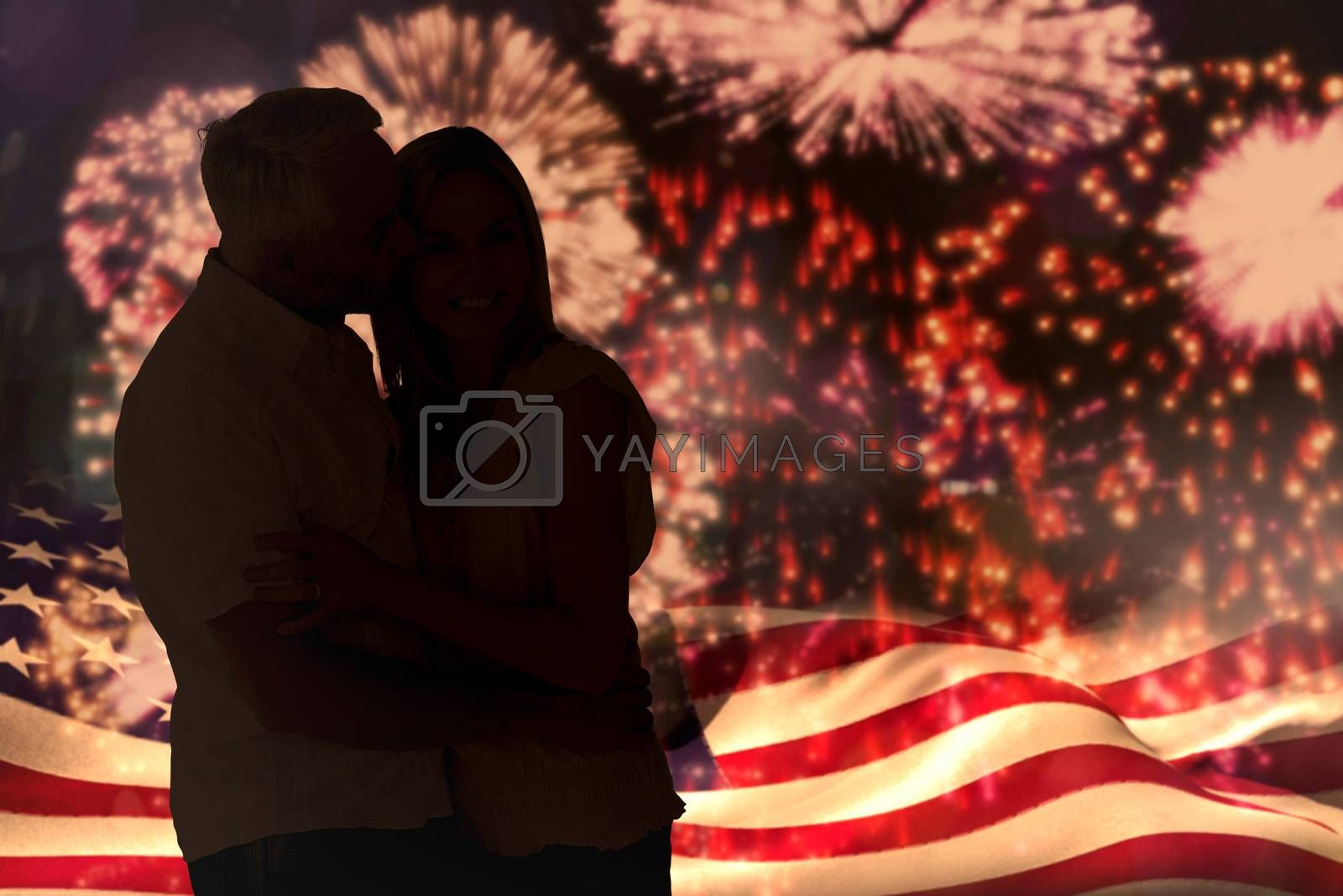 Affectionate man kissing his wife on the cheek against colourful fireworks exploding on black background