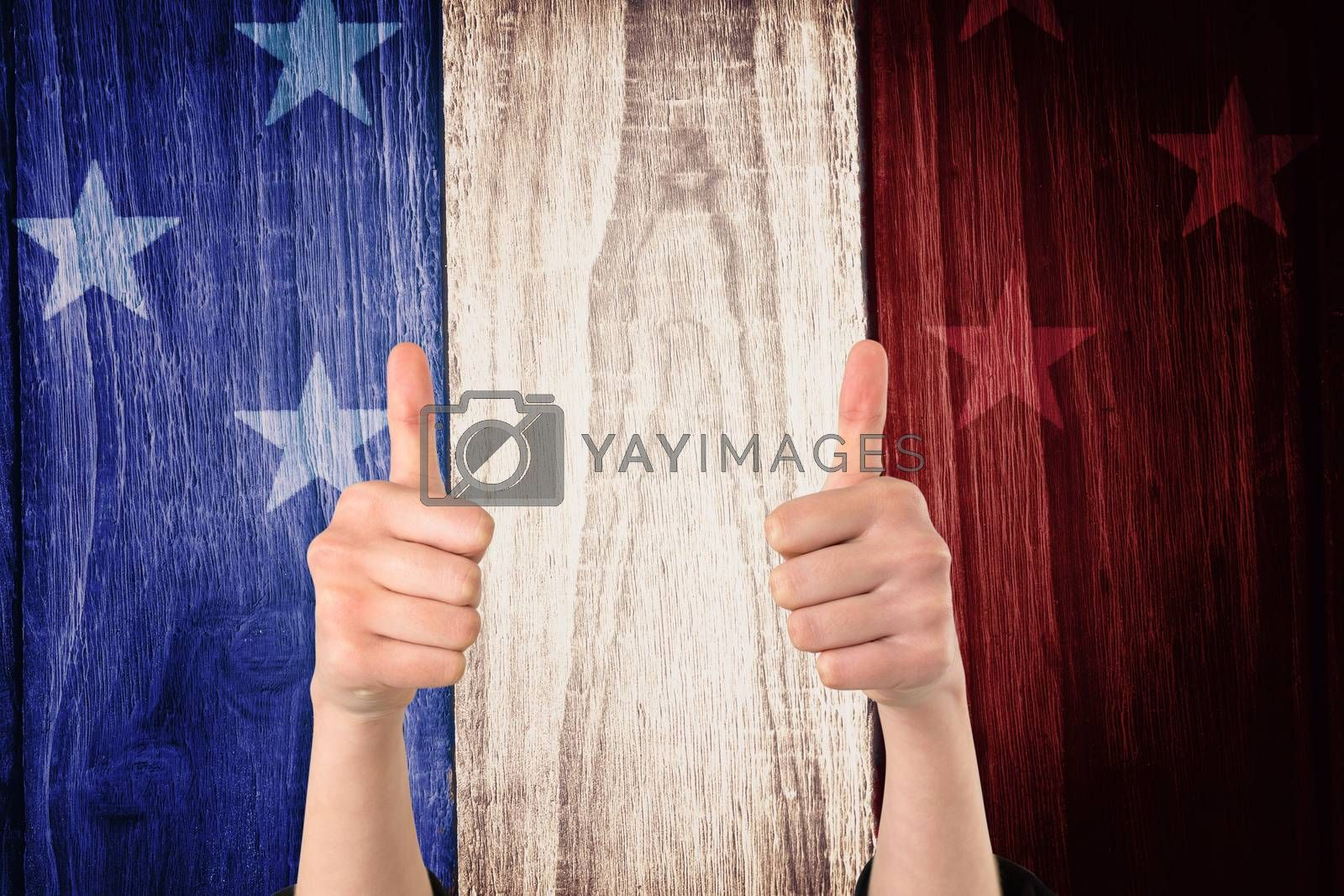 Businesswomans hands showing thumbs up against digitally generated grey wooden planks