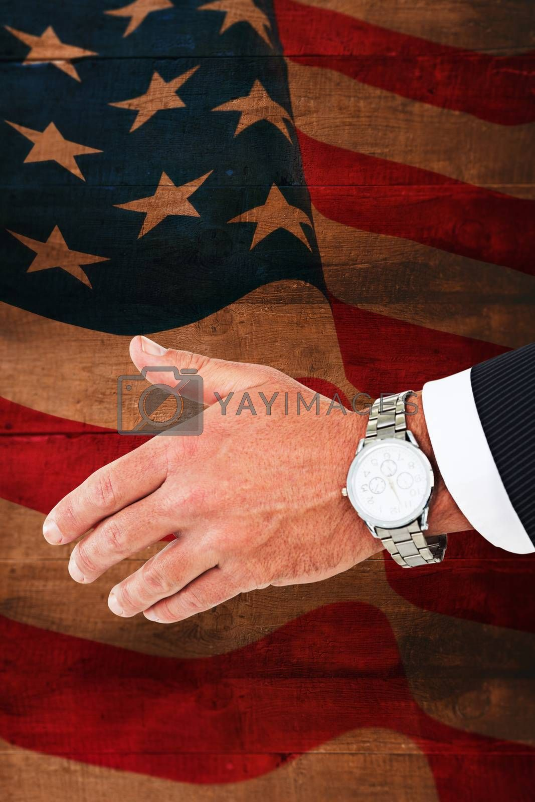 Businessman in suit clenching fists against weathered oak floor boards background