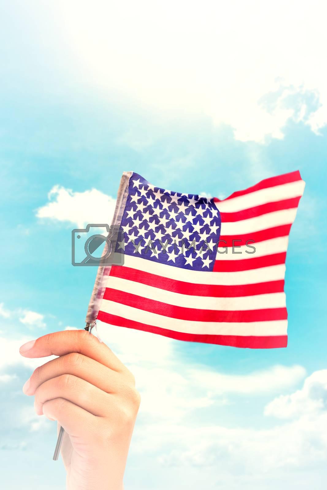 Hand waving american flag against blue sky