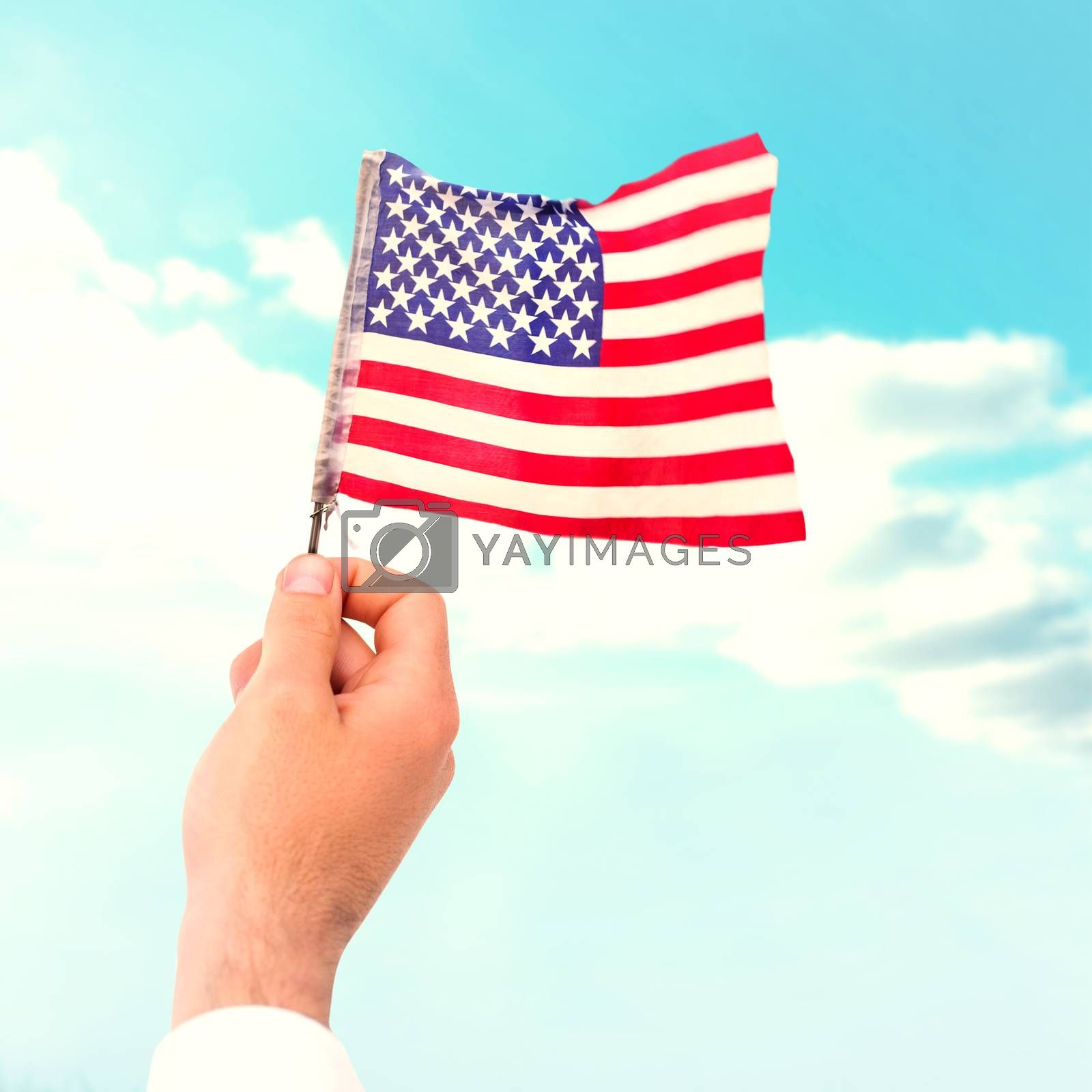 Hand waving american flag against blue sky over green field