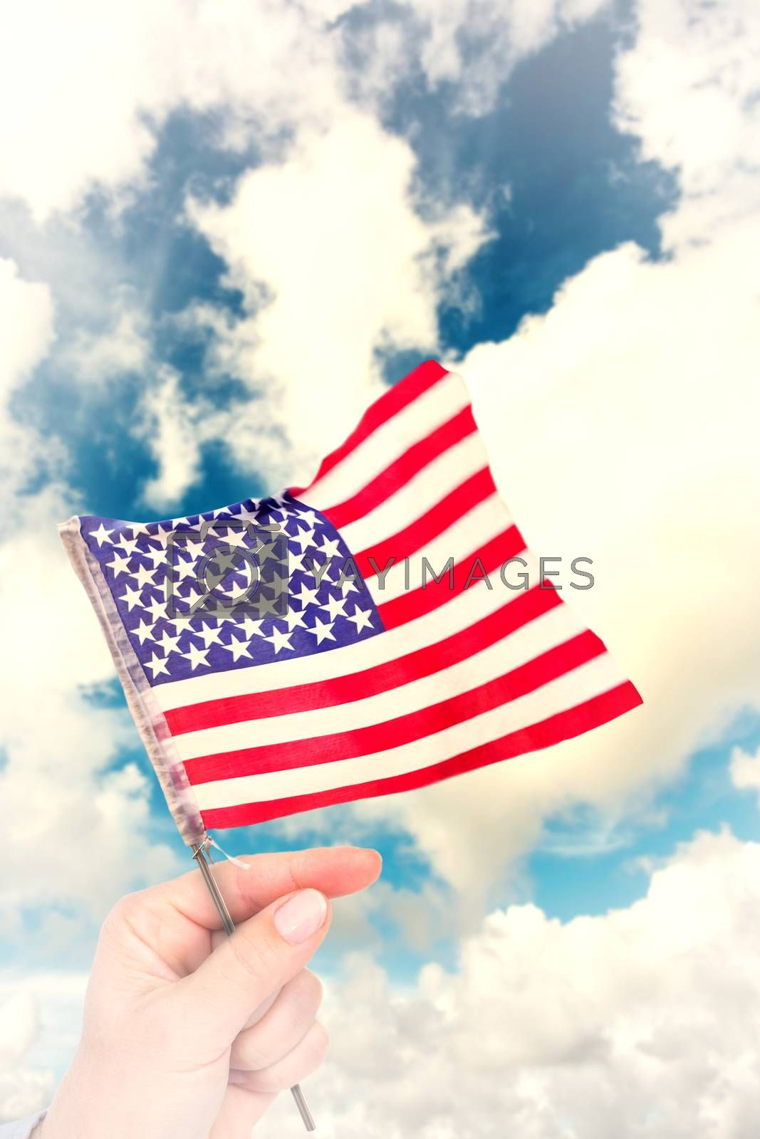 Hand waving american flag against blue sky with white clouds