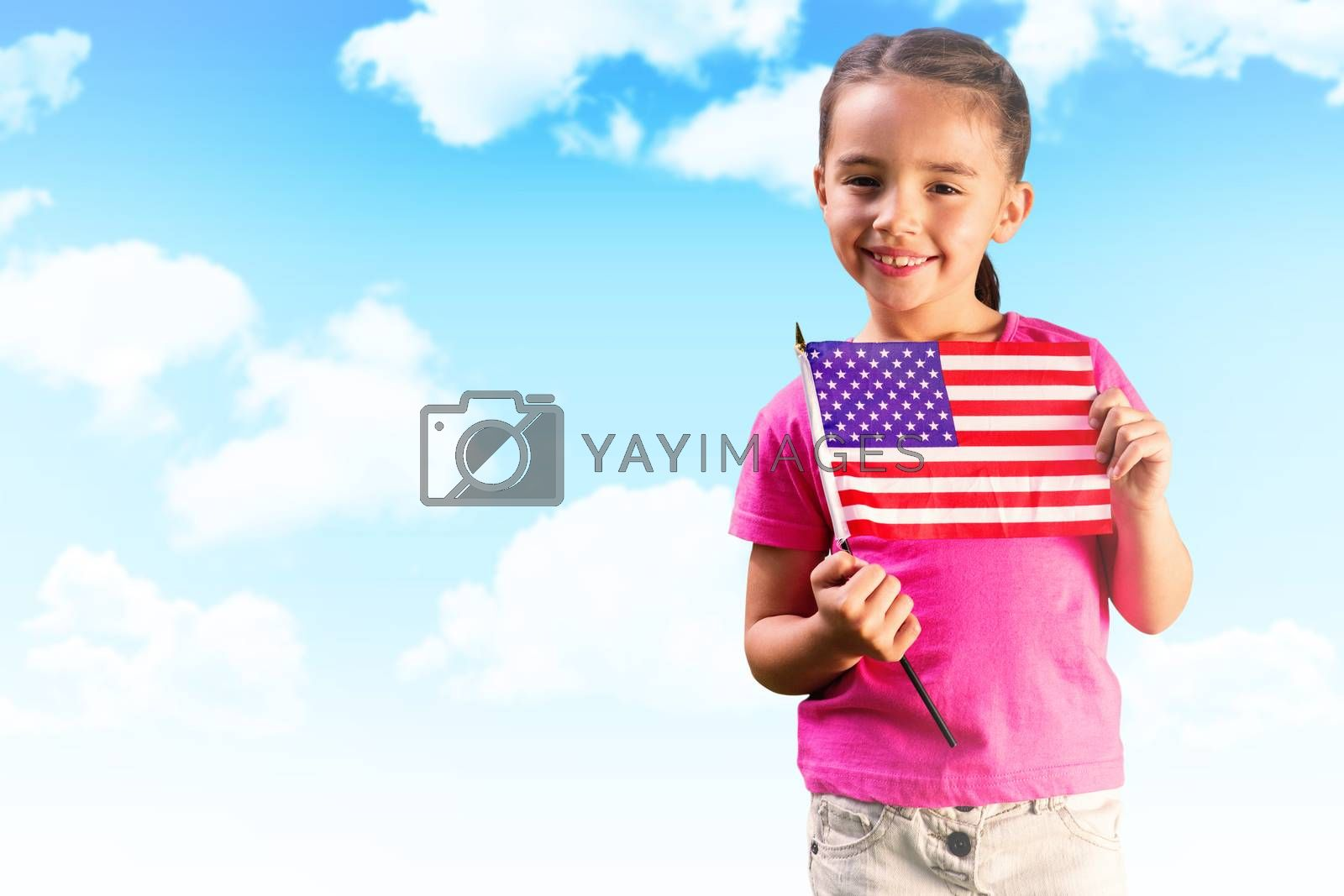 Little girl with american flag against blue sky