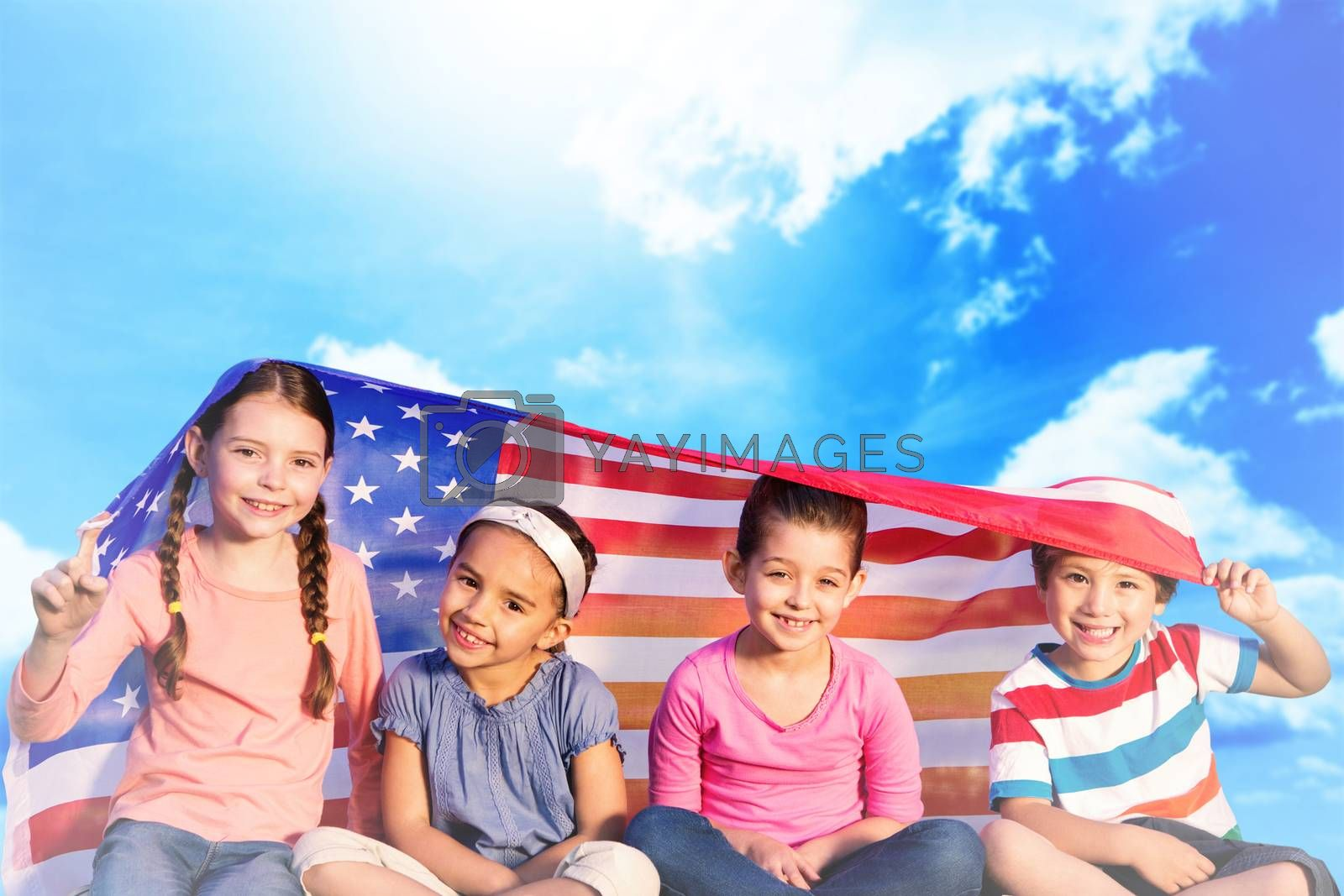 Children with american flag against blue sky