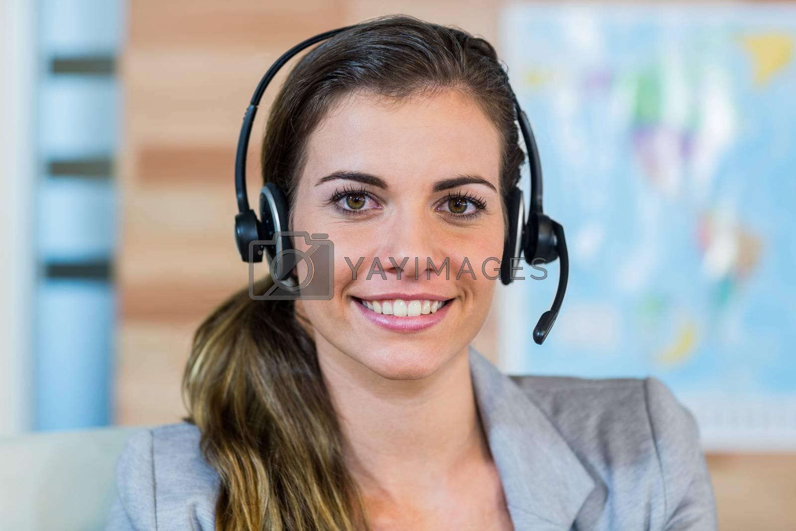 Pretty travel agent smiling at camera by Wavebreakmedia