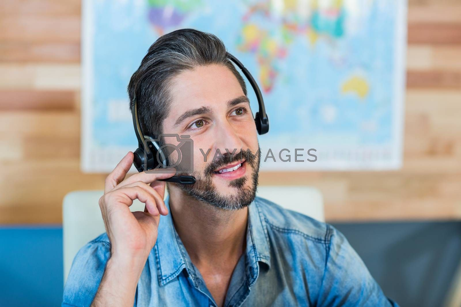 Smiling travel agent having phone call by Wavebreakmedia