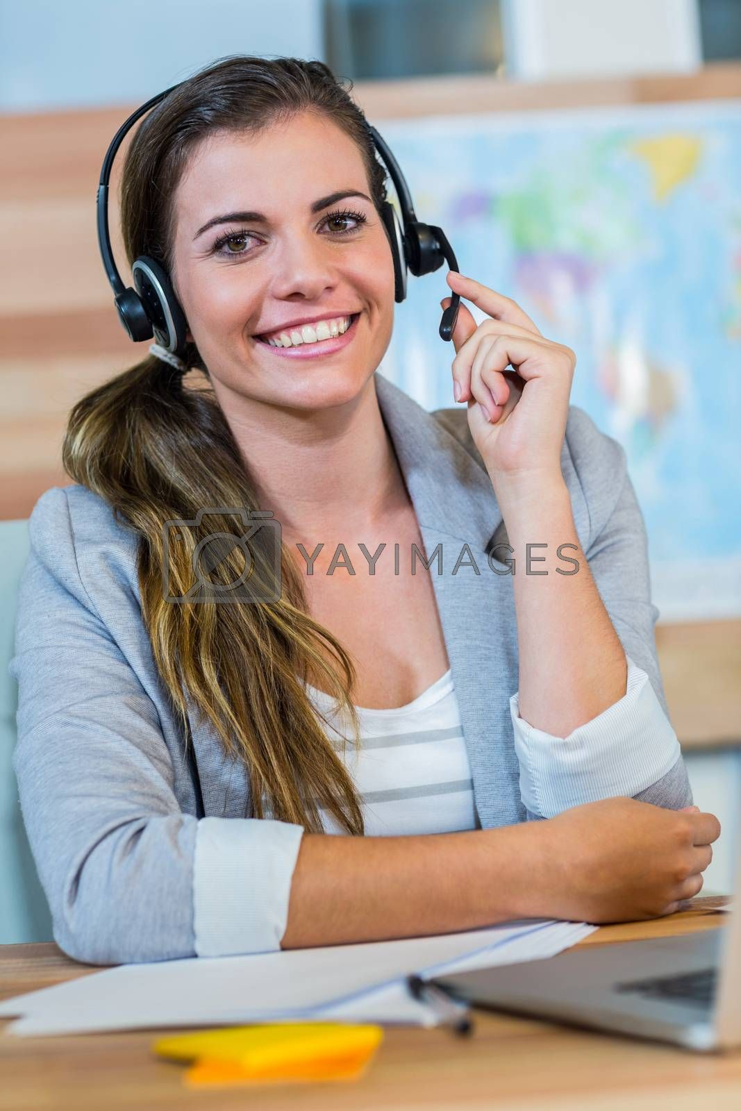 Pretty travel agent smiling at camera by Wavebreakmedia