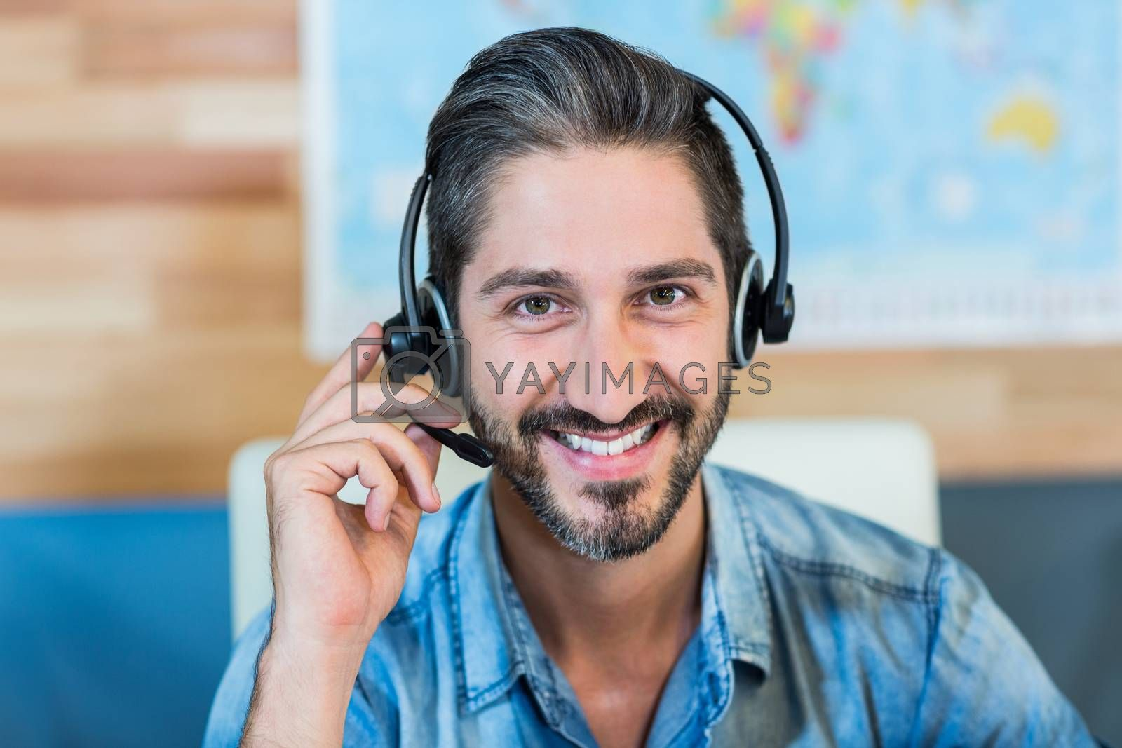Smiling travel agent looking at camera in the office