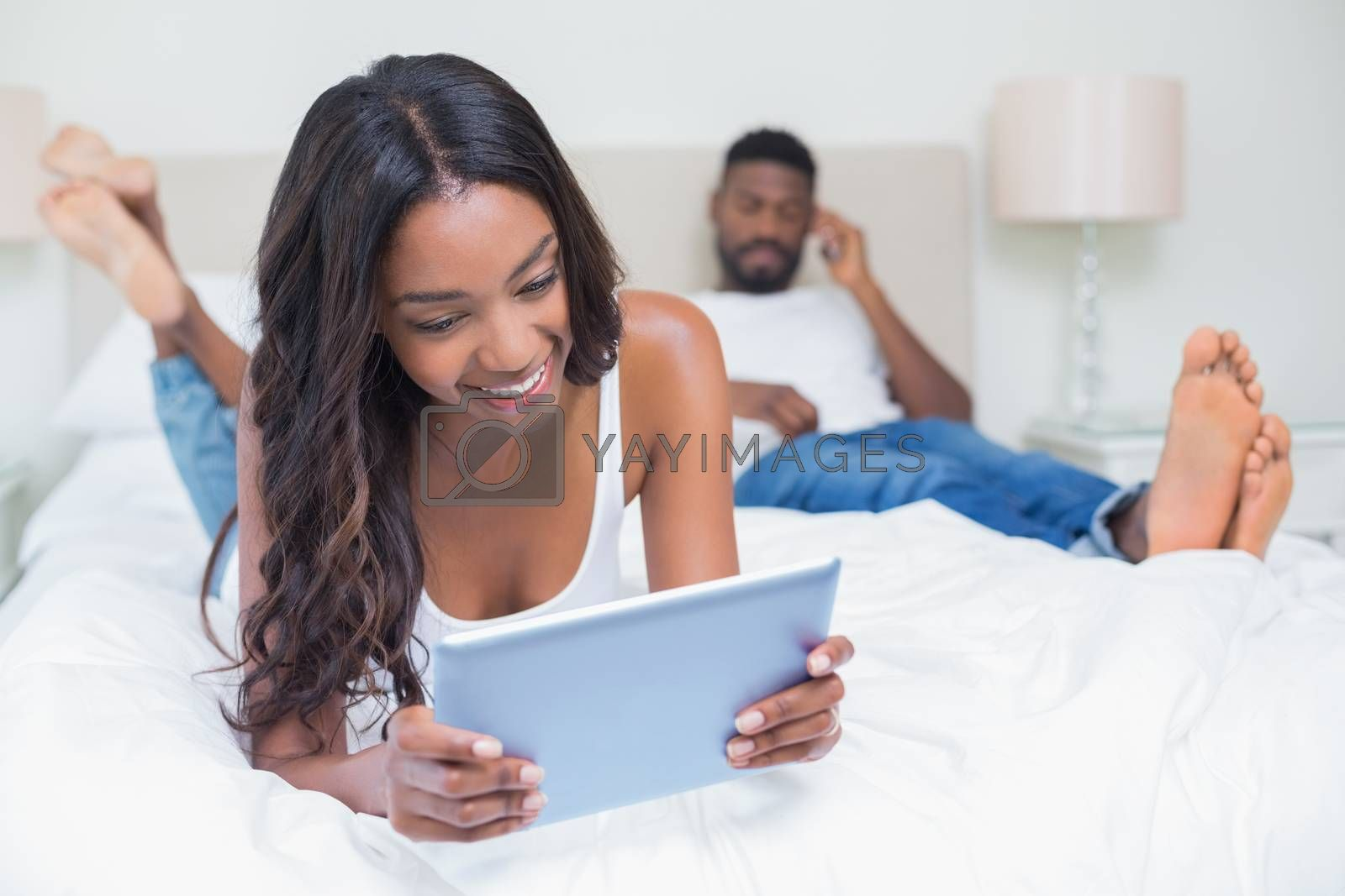 Relaxed couple using technology on bed at home in bedroom