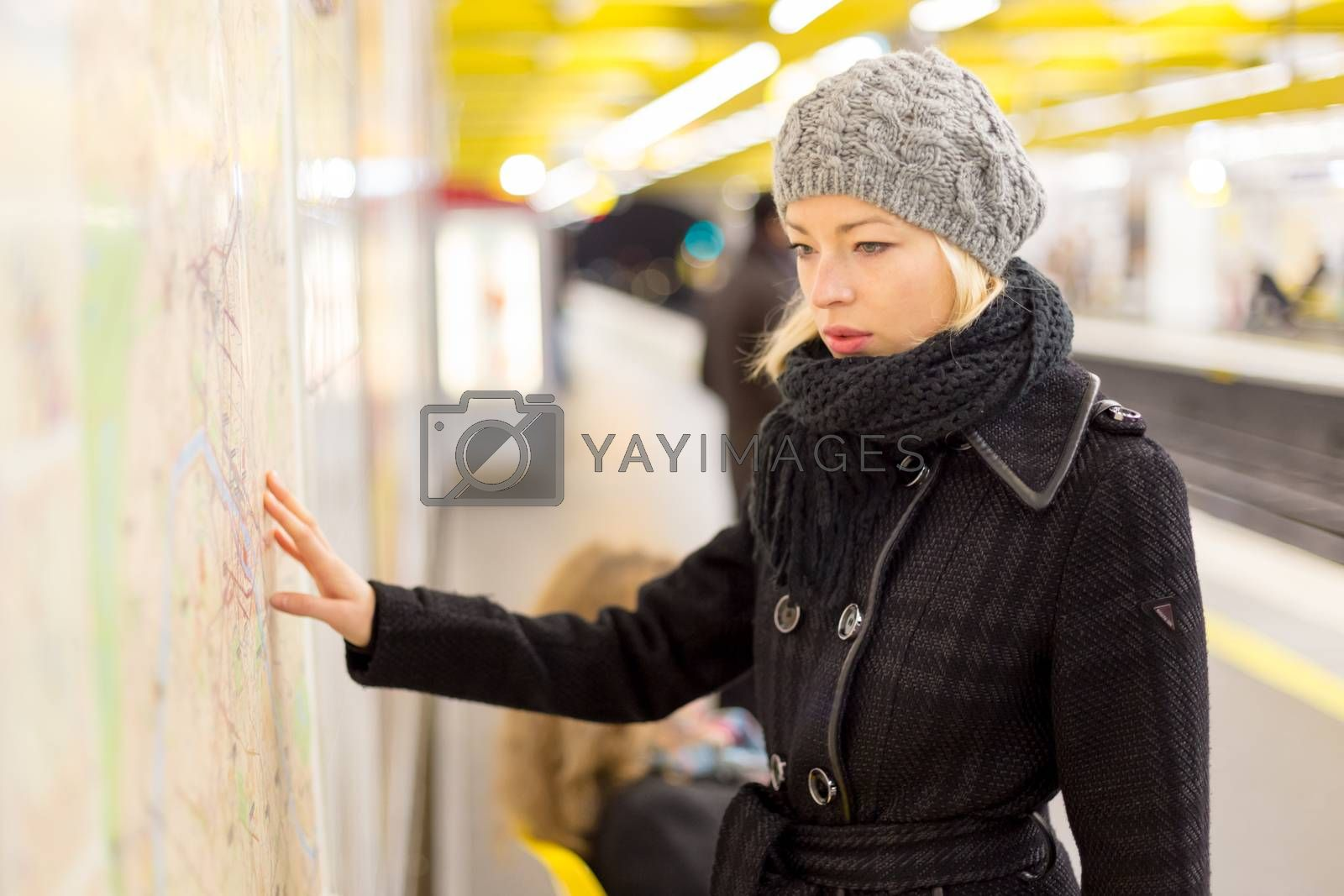 Casually dressed woman wearing winter coat, orientating herself with public transport map panel. Urban transport.