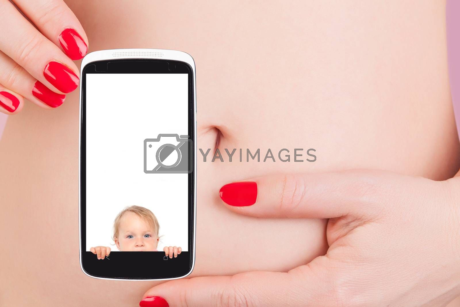 Sexy woman with red nails holding mobile phone with pregnancy test against her belly. The future of medicine, high tech.
