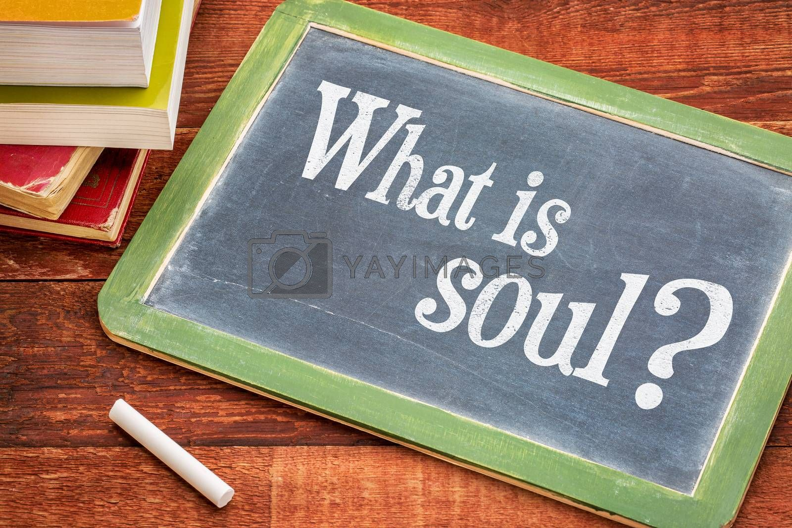 What is soul spiritual question on a slate blackboard with a white chalk and a stack of books against rustic wooden table