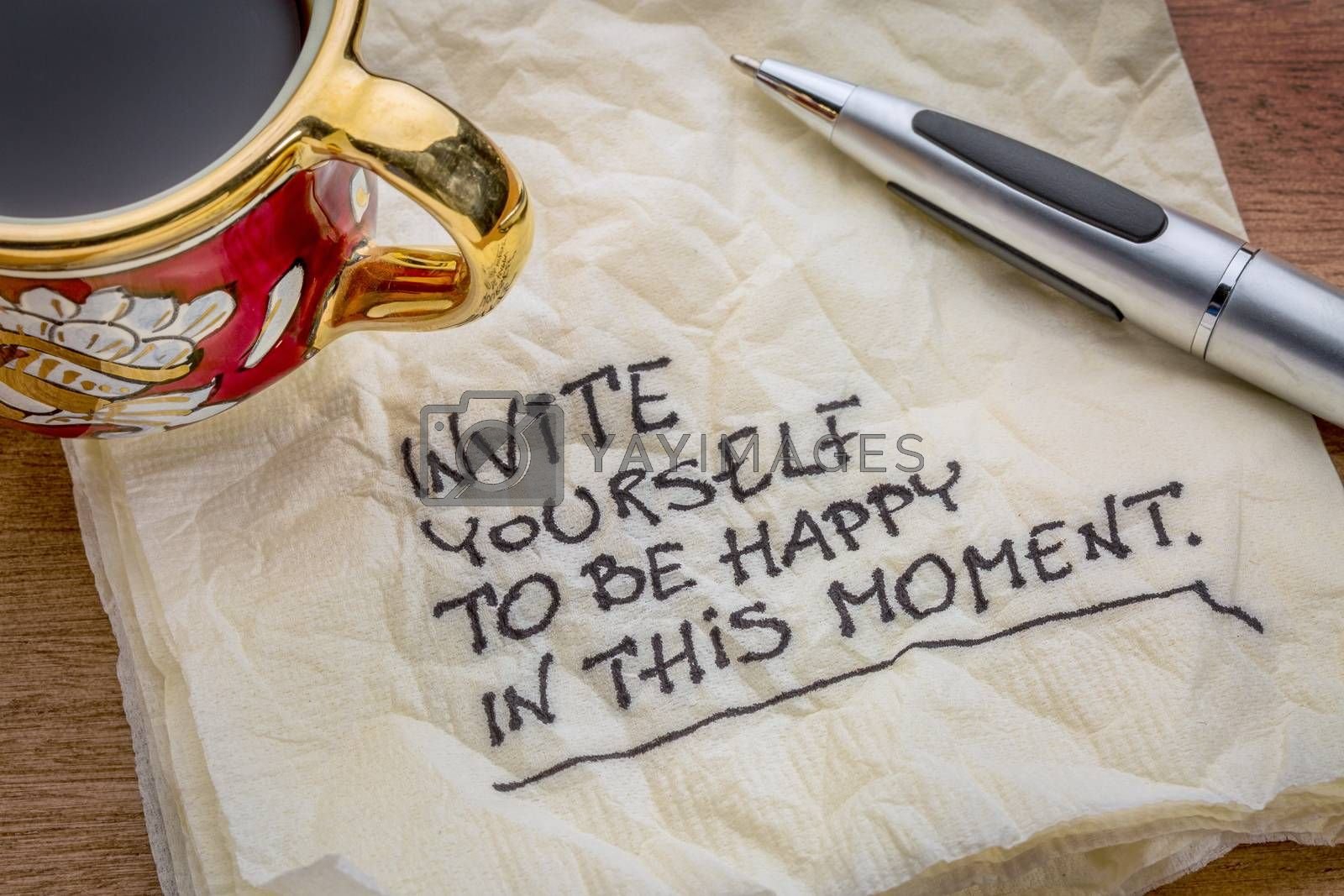Invite yourself to be happy in this moment - inspirational advice on a napkin with a cup of coffee