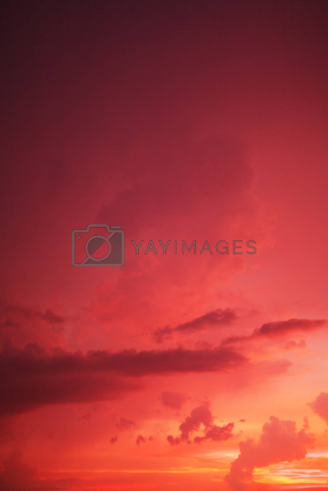 Dramatic red sunset sky with a fiery glow from the setting sun in a weather and nature full frame background, vertical orientation