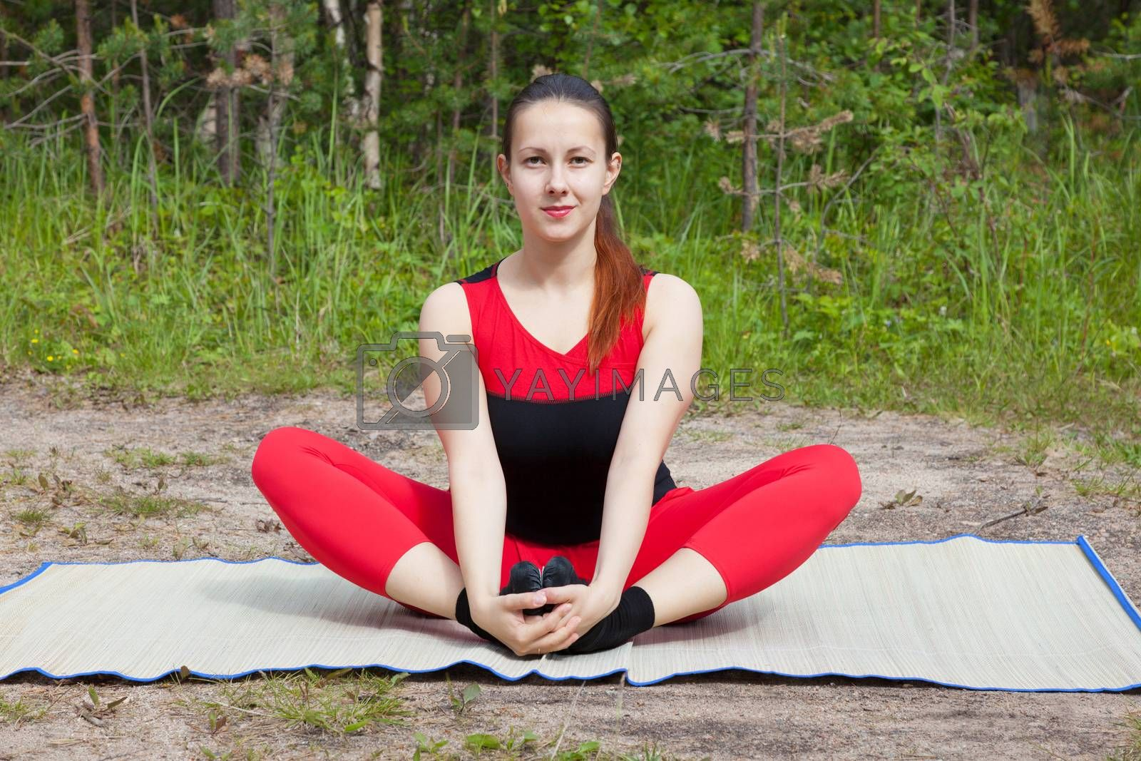 The young girl engaged in yoga class in a forest glade