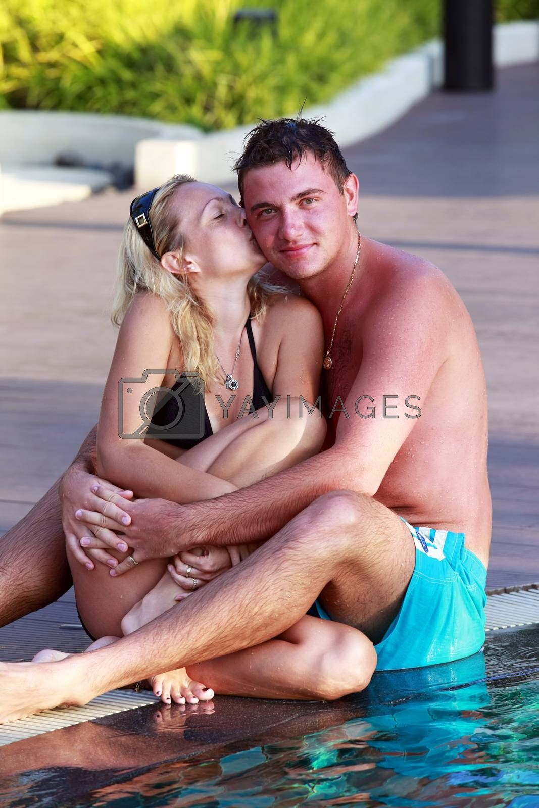Beautiful lovers relaxing and embraces and kisses in swimming pool