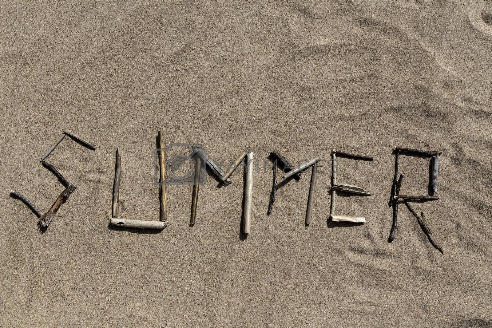 A set of sticks in a sandy beach forming the word Summer