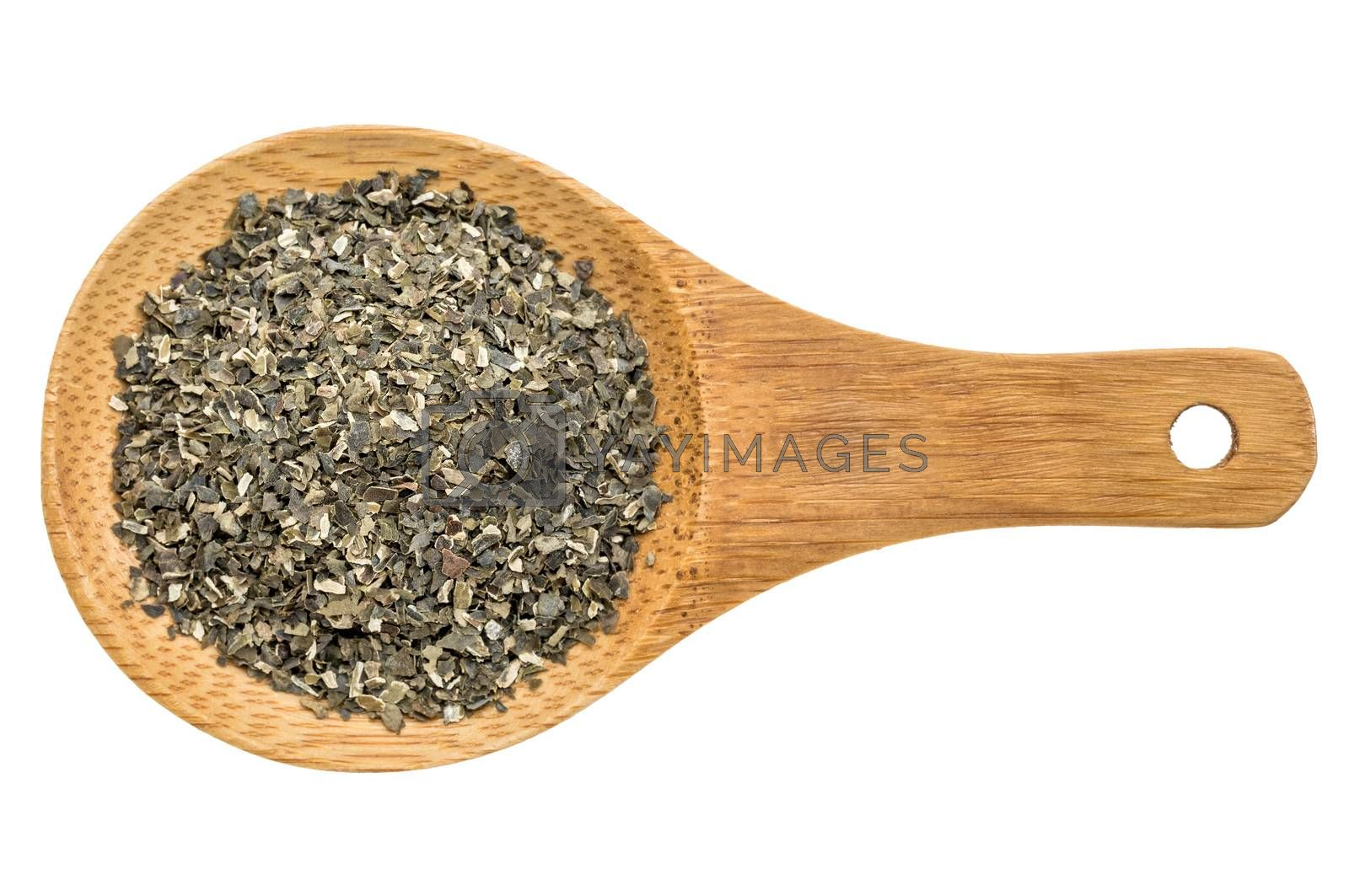 dried wakame seaweed - top view of a wooden spoon isolated on white