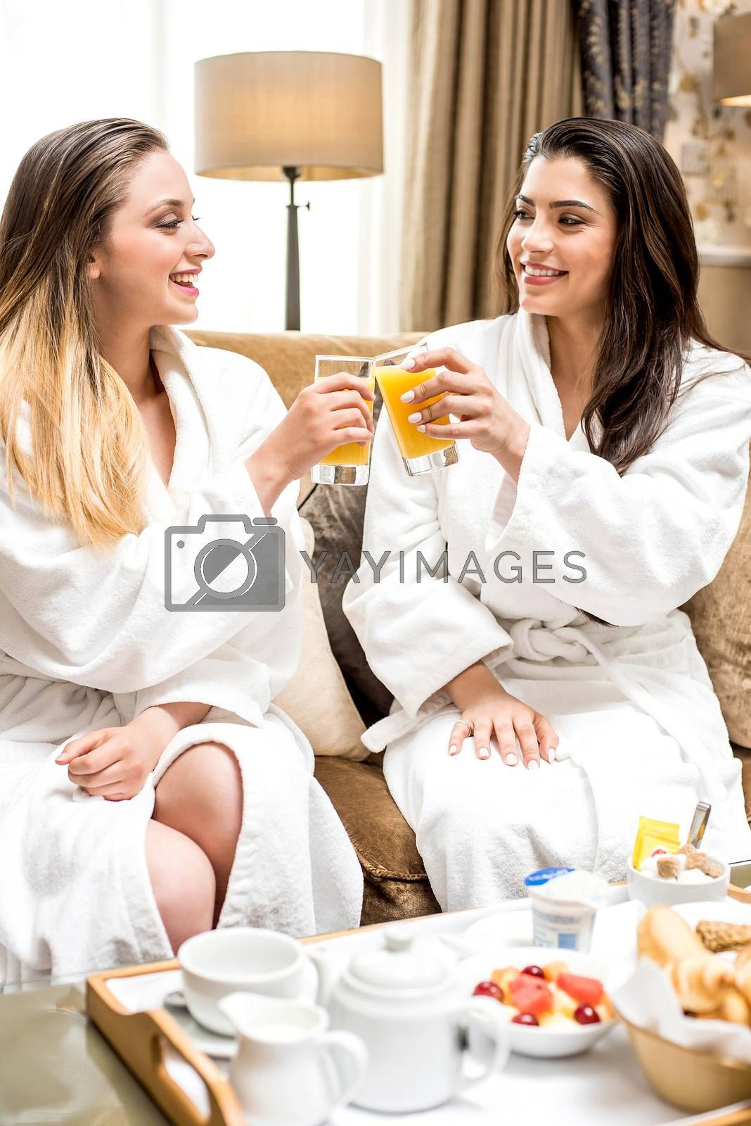 Two  beautiful female friends drinking juice on sofa