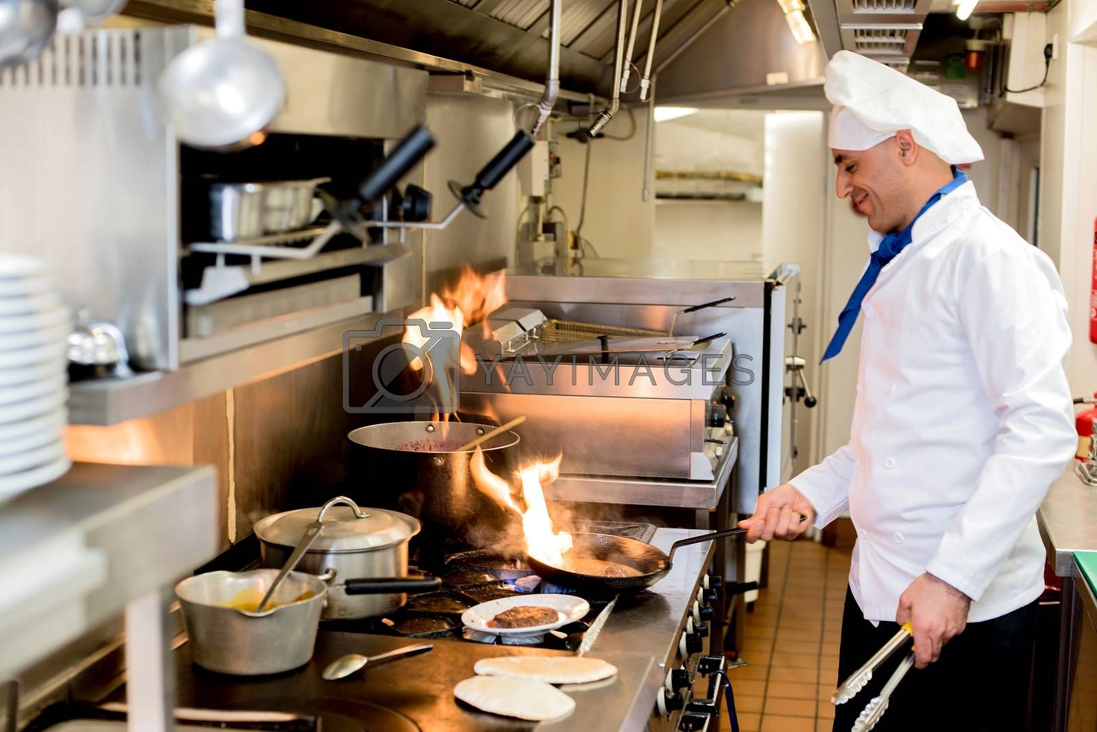 Male chef cooking with flame in a frying pan on kitchen
