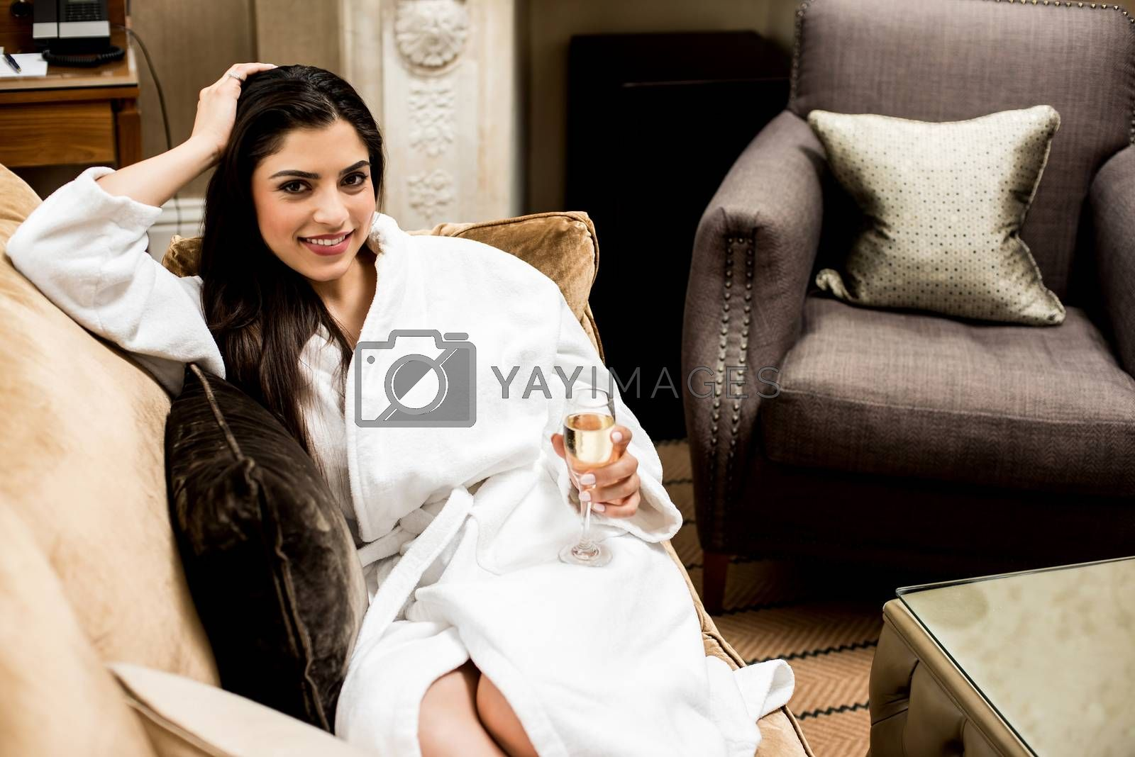Relaxed woman laying in sofa with glass of champagne