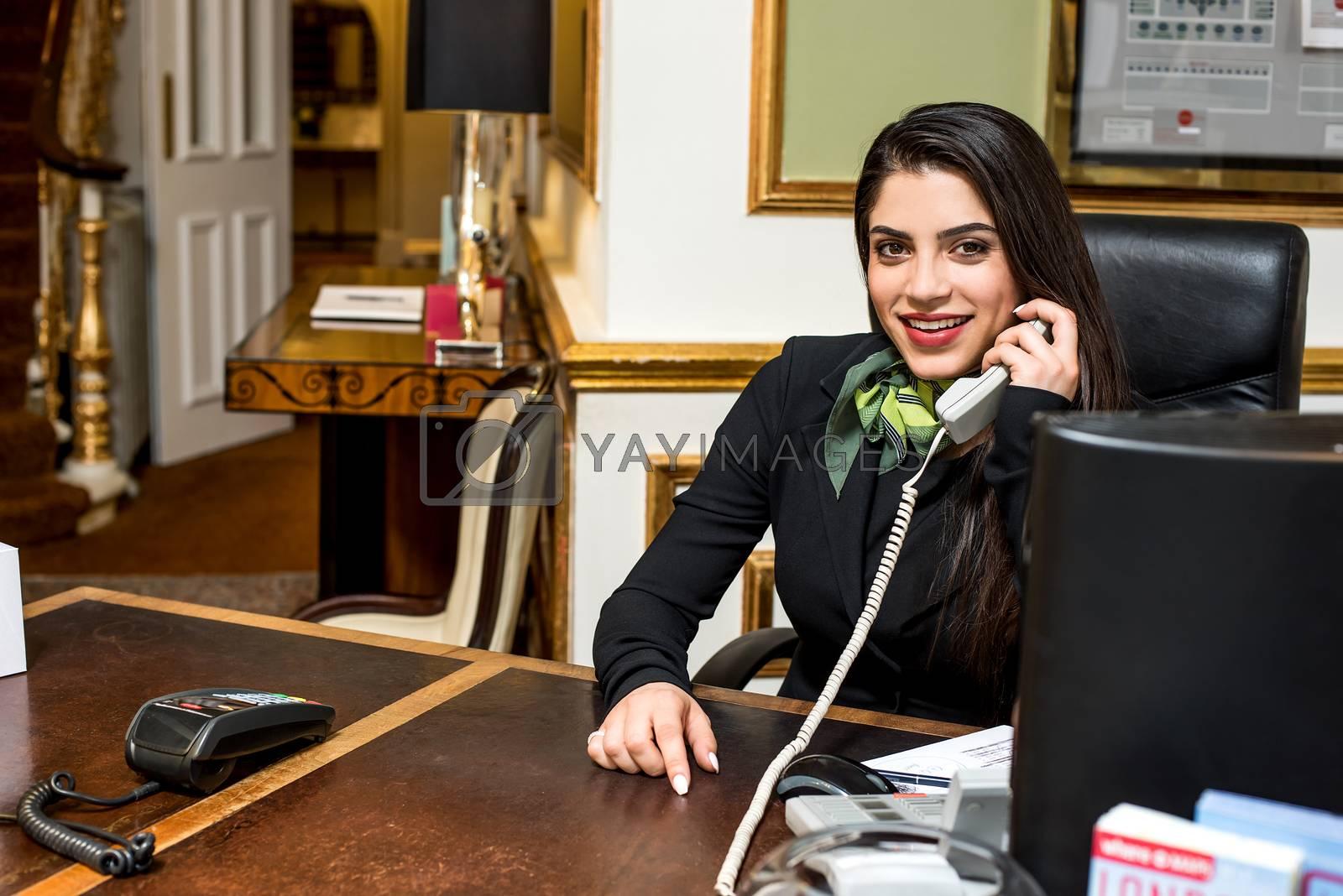 Smiling stylish receptionist talking on telephone