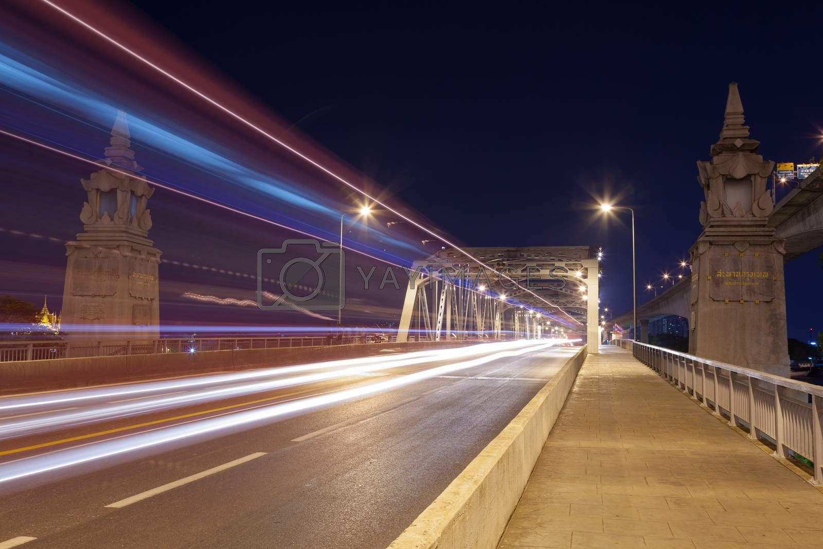 Traffic at night. The light from cars traveling across the bridge at night.