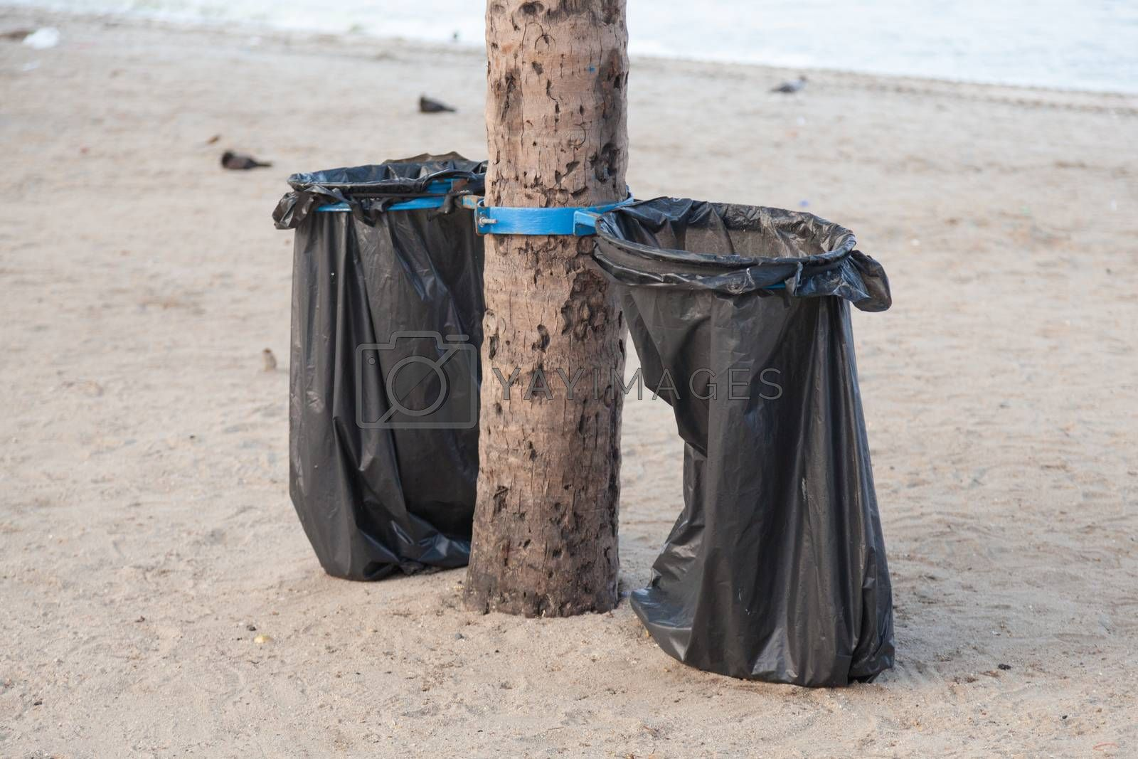 Black garbage bags. Plastic black trash on the beach under the coconut trees.