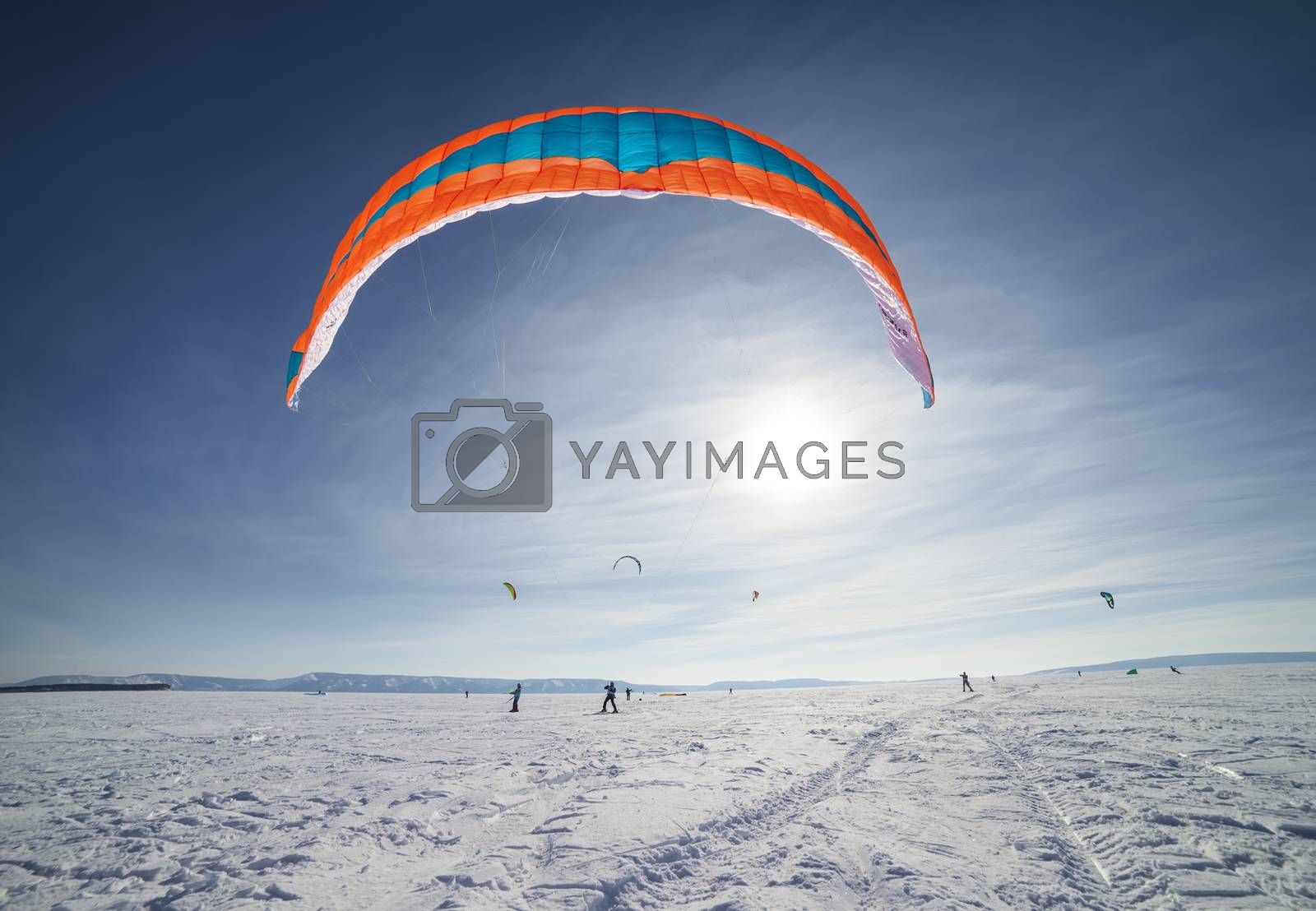 Kite surfer being pulled by his kite across the snow